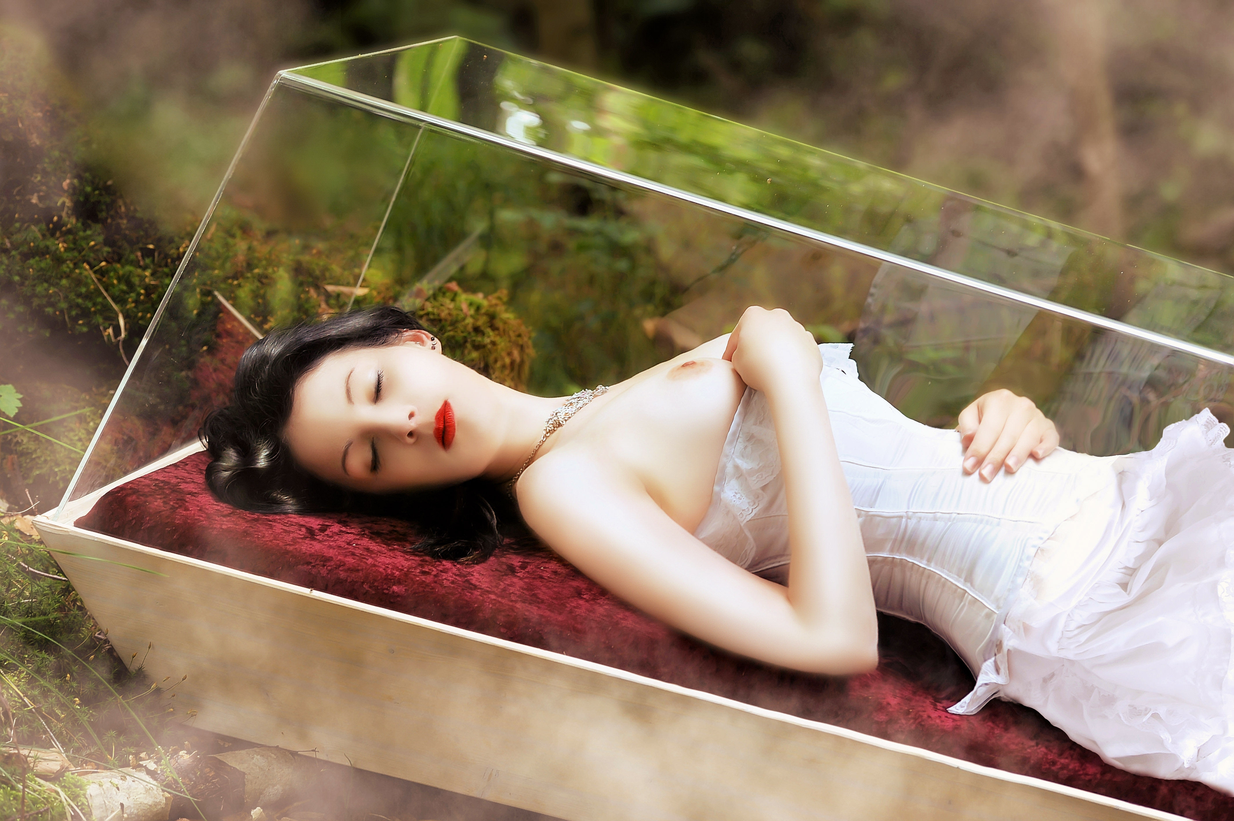 Фото Спящая красавица в белом платье в стеклянном гробу и голыми сиськами, красные губы, скачать картинку бесплатно