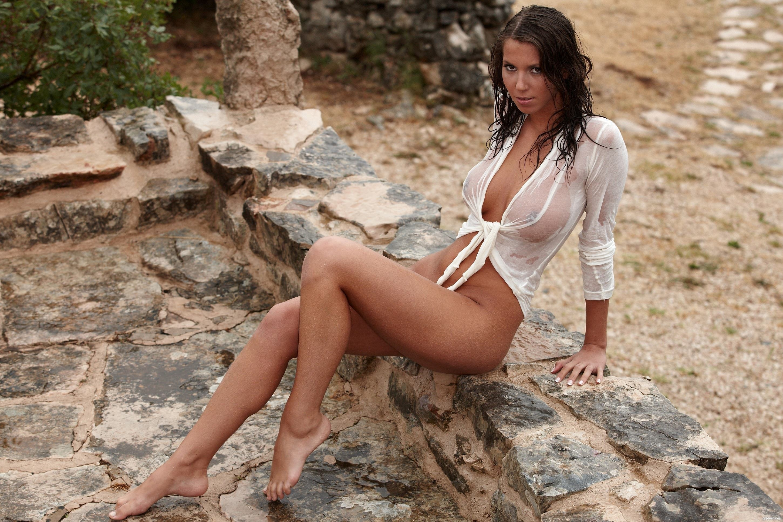 Фото Сексапильная мокрая брюнетка с соблазнительным взглядом сидит на камнях, сексуальные загорелые ножки, белая промокшая блузка, сиськи видно насквозь, скачать картинку бесплатно