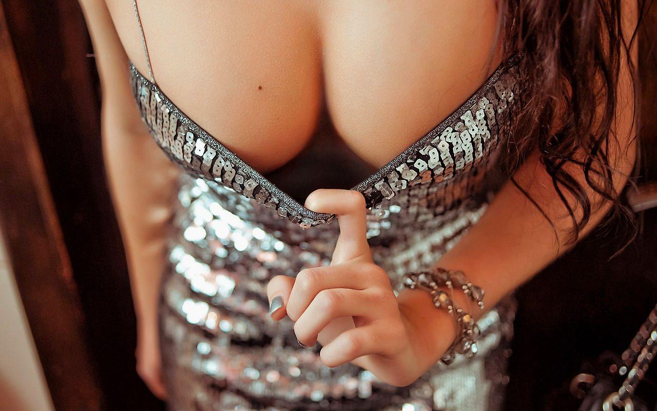 Фото Девушка в вечернем серебристом платье, натянула платье в районе декольте, почти оголив грудь, сиськи в платье. The girl in a silvery evening dress with a deep decollete, nice tits, скачать картинку бесплатно