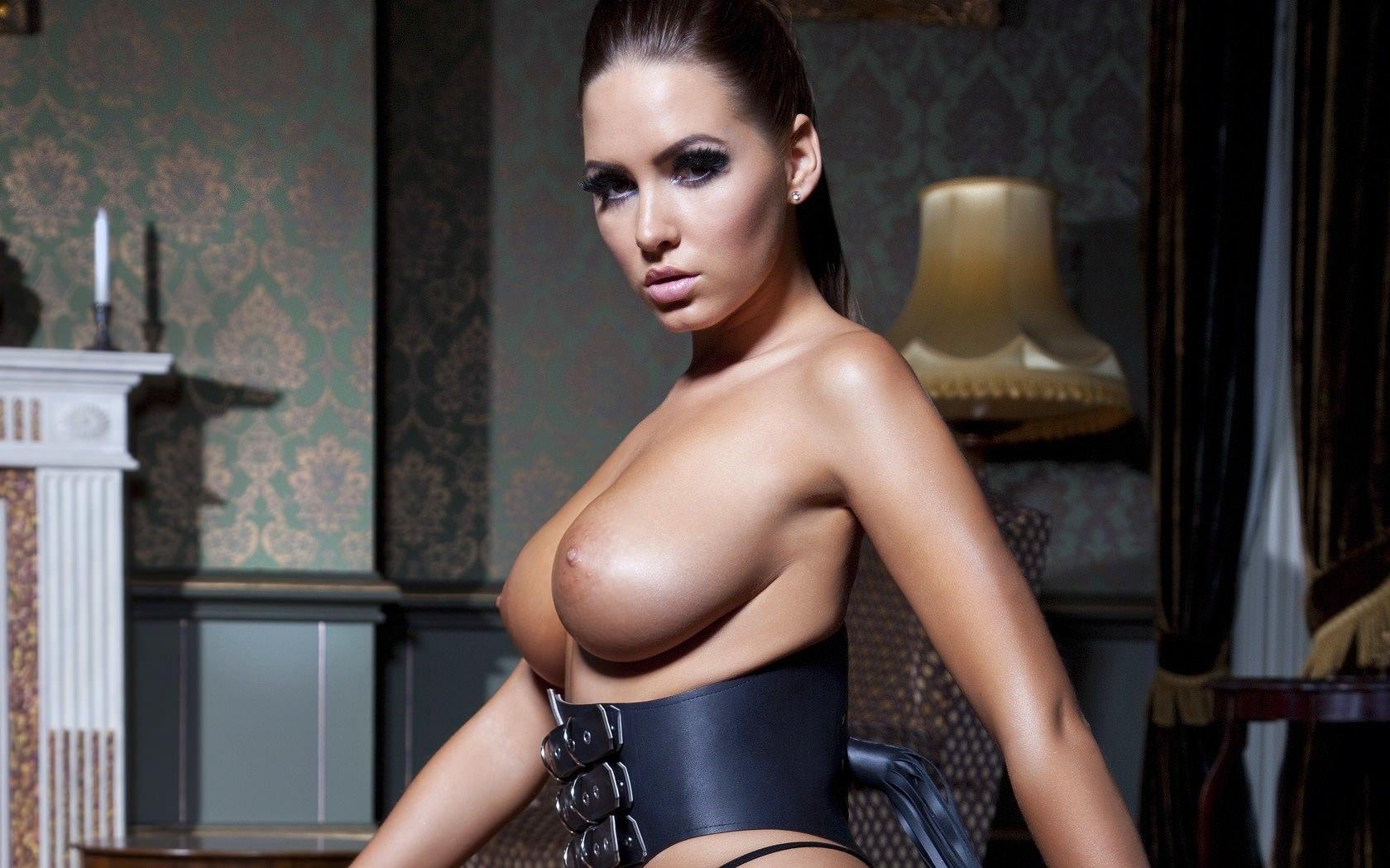 Фото Сексуальная брюнетка в черном корсете до груди, большие красивые голые сиськи, соблазнительная девушка с обнаженной грудью в комнате с камином. Sexy brunette in the room, black corset, naked boobs, sexy tits, sexy body, shiny tits, скачать картинку бесплатно