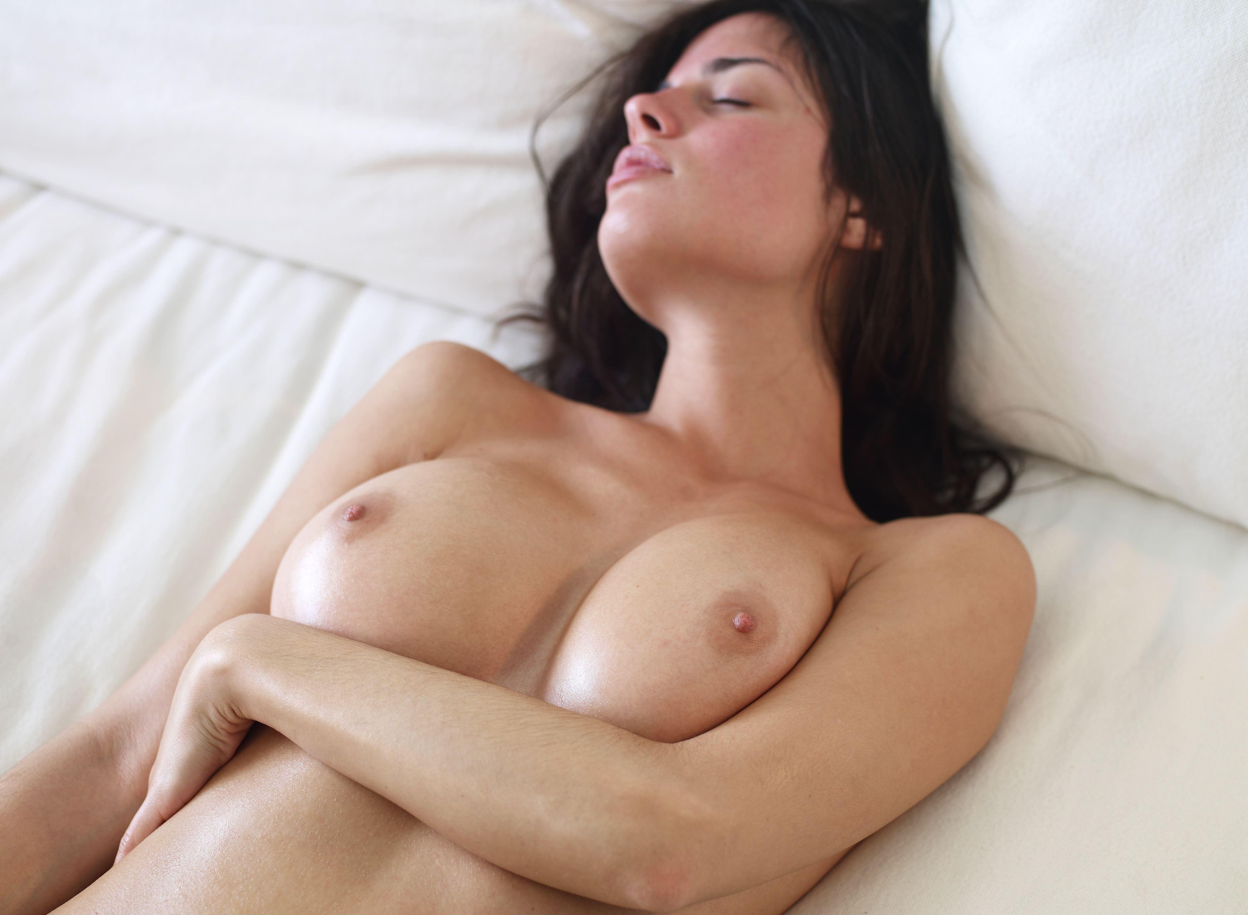 Фото Возбужденная молодая девушка лежит голая в постели утром, красивые упругие сиськи, натуральная красивая грудь блестит на солнце, брюнетка на кровати, сексуальное тело, сладкие соски, сочные сиськи. Naked brunette on the bed, sexy, seductive, temptation, nice tits, pink nipples, shiny boobs, erotic, скачать картинку бесплатно