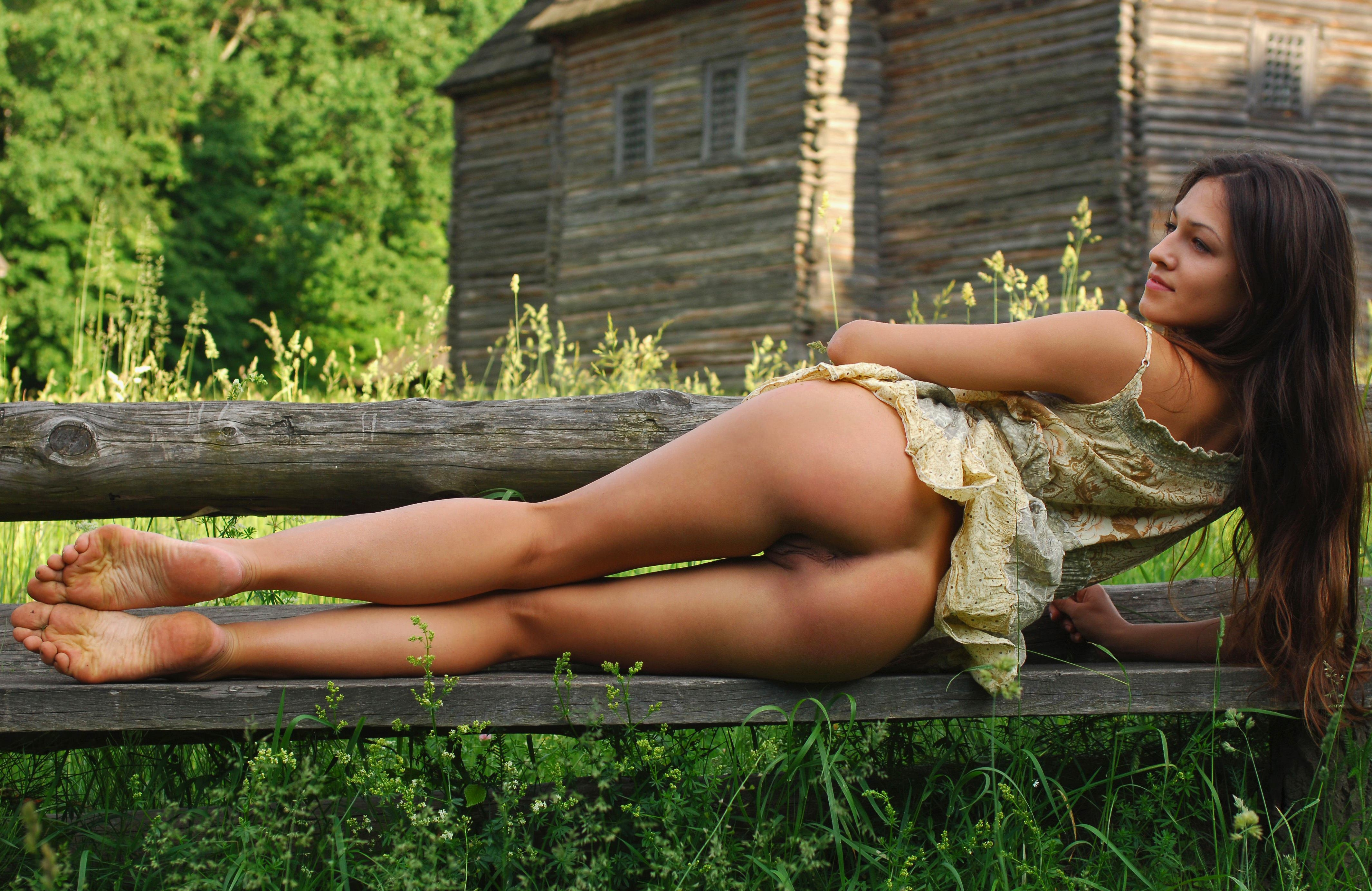 Beautiful implied nude woman in grass with flowers stock photo