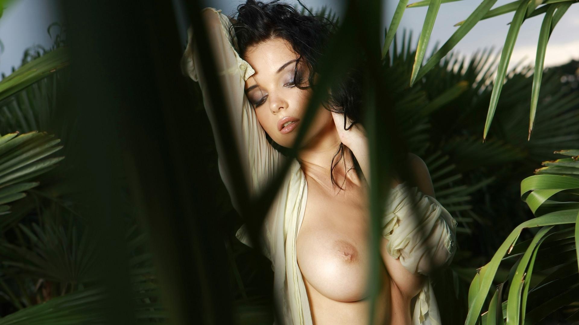 Фото Сексуальная девушка соблазнительно извивается среди кустов, голая грудь, жгучая брюнетка в джунглях, скачать картинку бесплатно