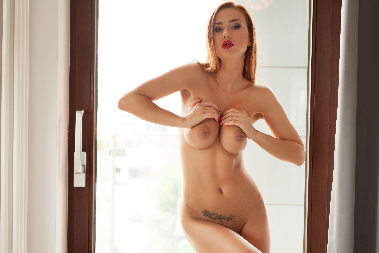 Фото Сексуальная рыжеволосая девушка возбужденно сжимает сиськи, пирсинг в сосках, тату ниже пупка, красные губки, сексуальное тело, аппетитная грудь, скачать картинку бесплатно