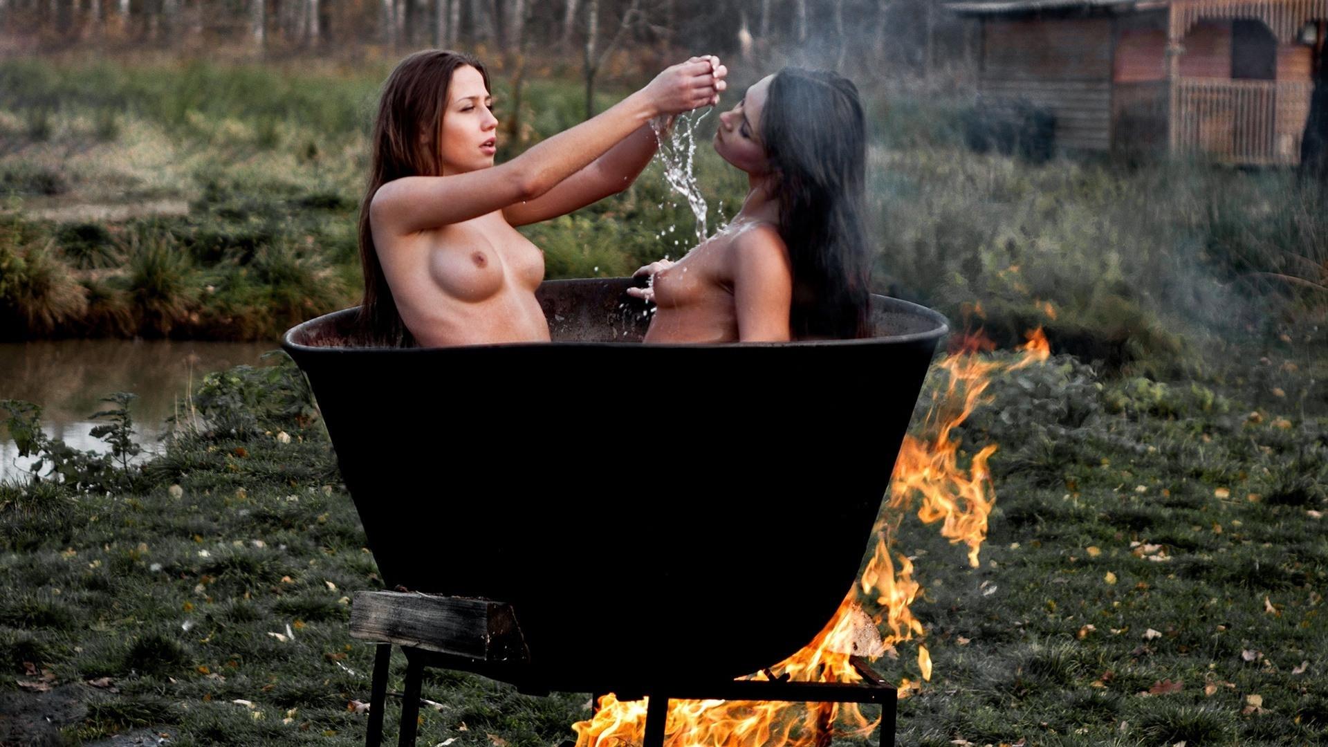 Фото Две голые девушки варятся в котле, голые брюнетки в чане с горячей водой под костром, скачать картинку бесплатно
