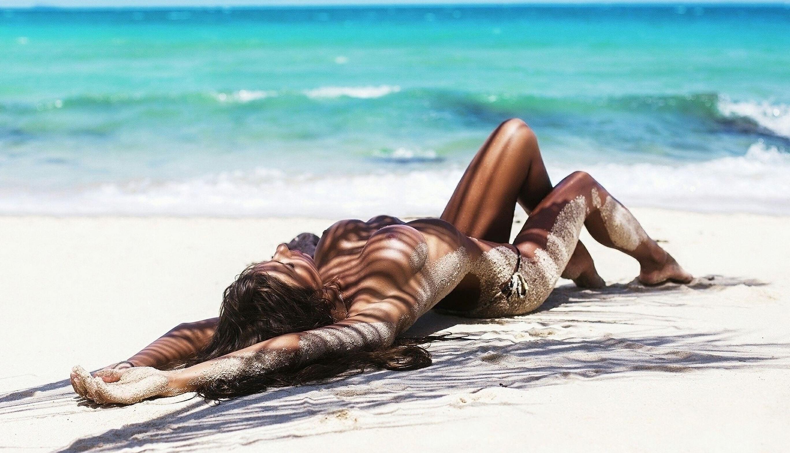 Фото Голая девушка на песке, море, пляже, песок, жара, сексуальное загорелое тело в песке, скачать картинку бесплатно