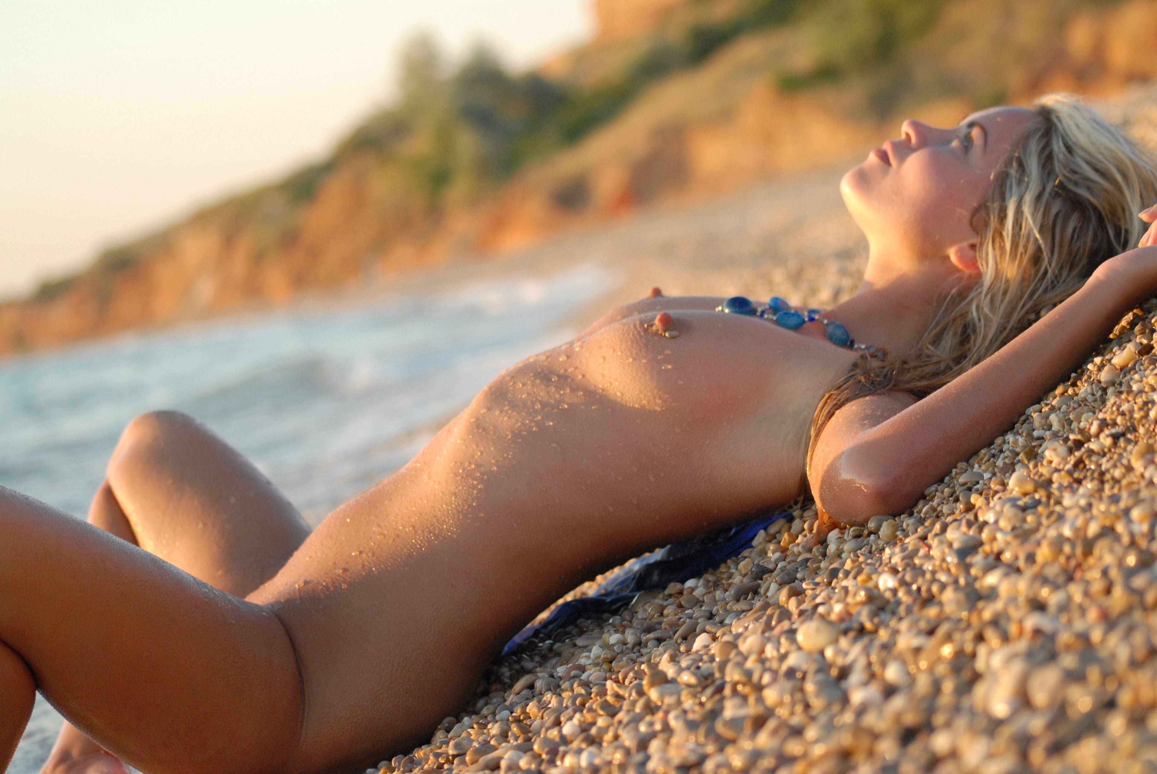 Фото Голая девушка разлеглась на гальке у моря, твердые набухшие соски, мокрая обнаженная блондинка на пляже в одиночестве, натуральная грудь, красивые мокрые небольшие сиськи, скачать картинку бесплатно