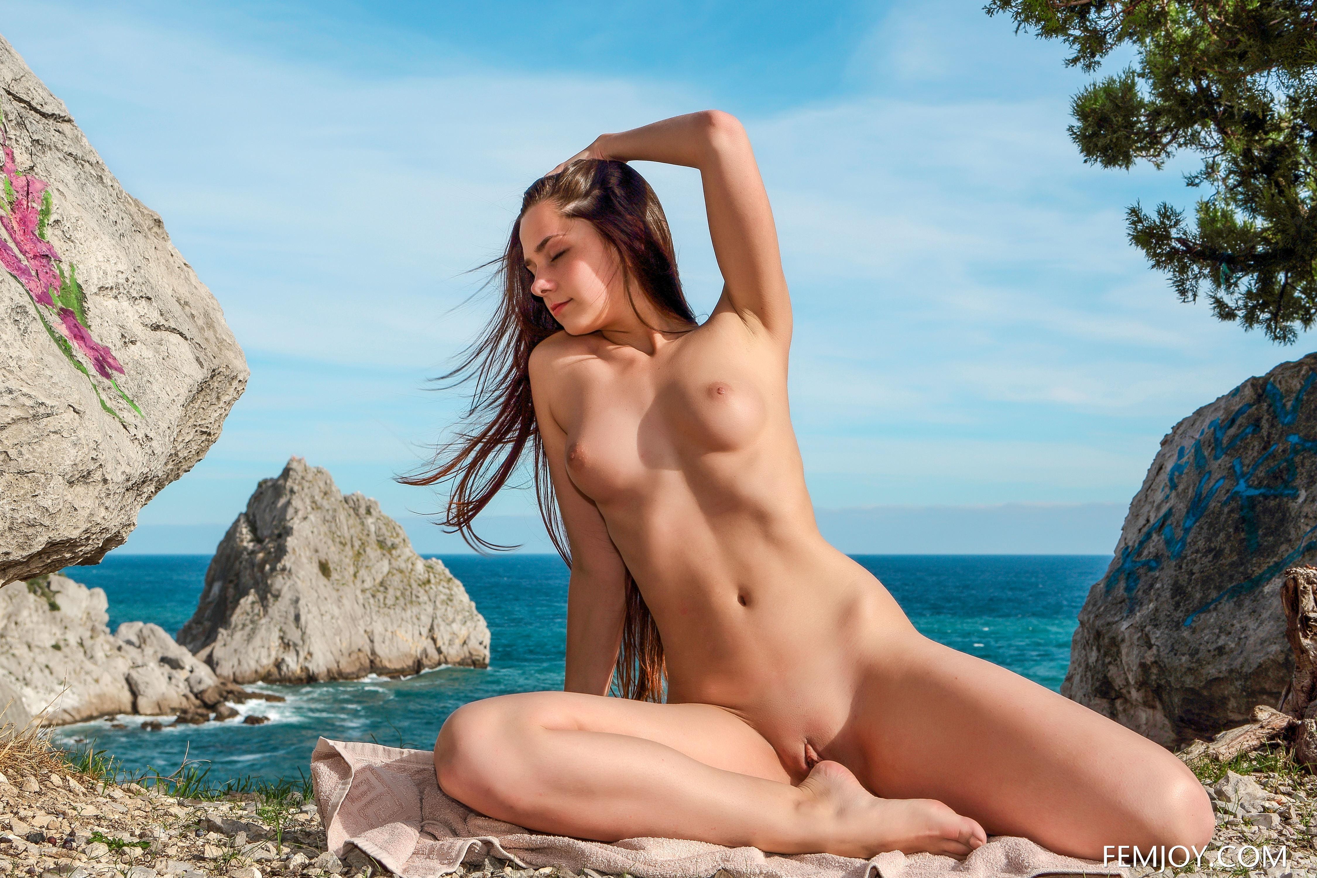 Фото Обнаженная девушка позирует на форе голубого моря возле скал, сексуальное тело молодой брюнетки, скачать картинку бесплатно