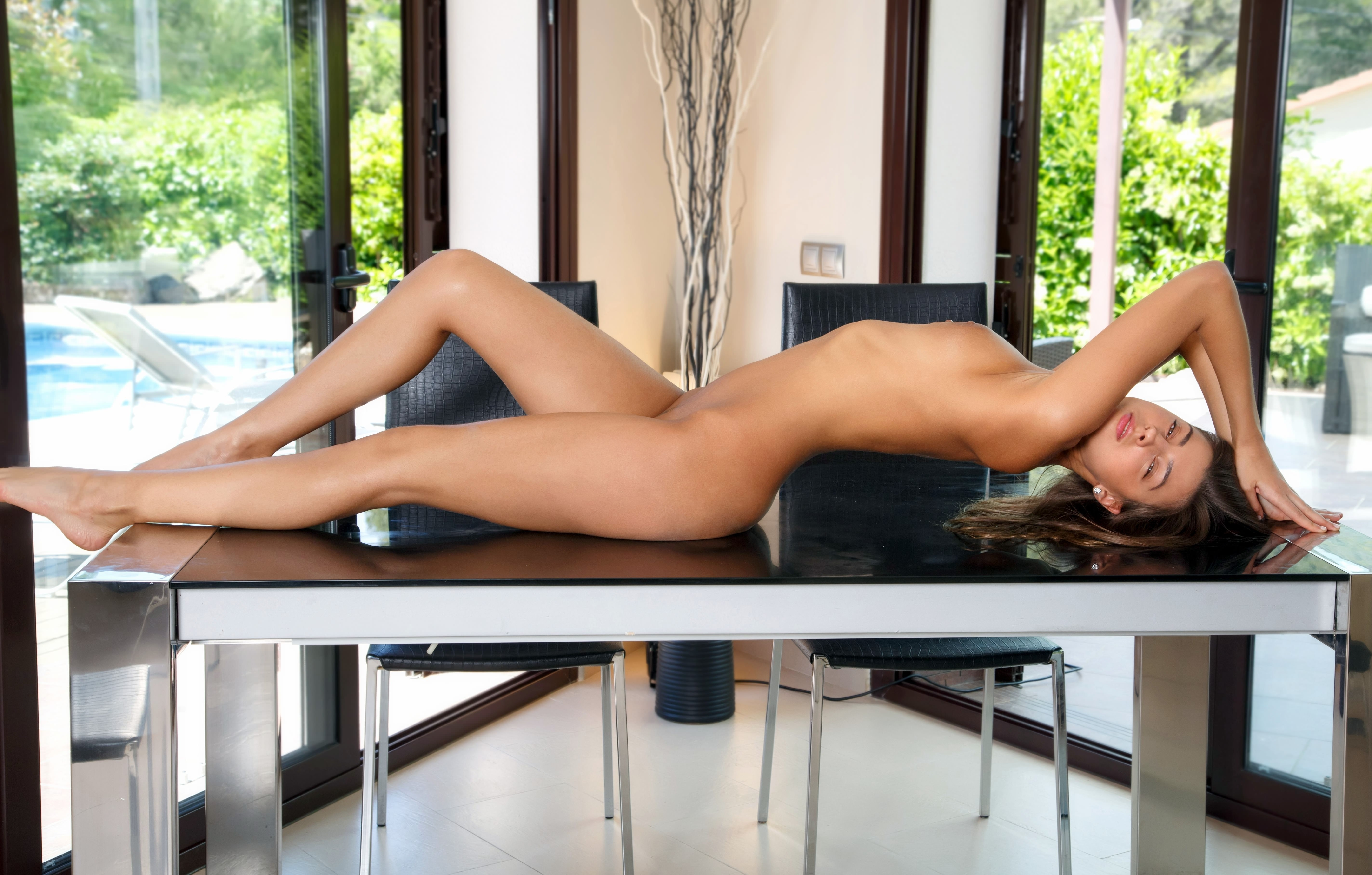 Фото Голая девушка позирует на кухонном столе, сексуальное вытянулась в струнку, скачать картинку бесплатно