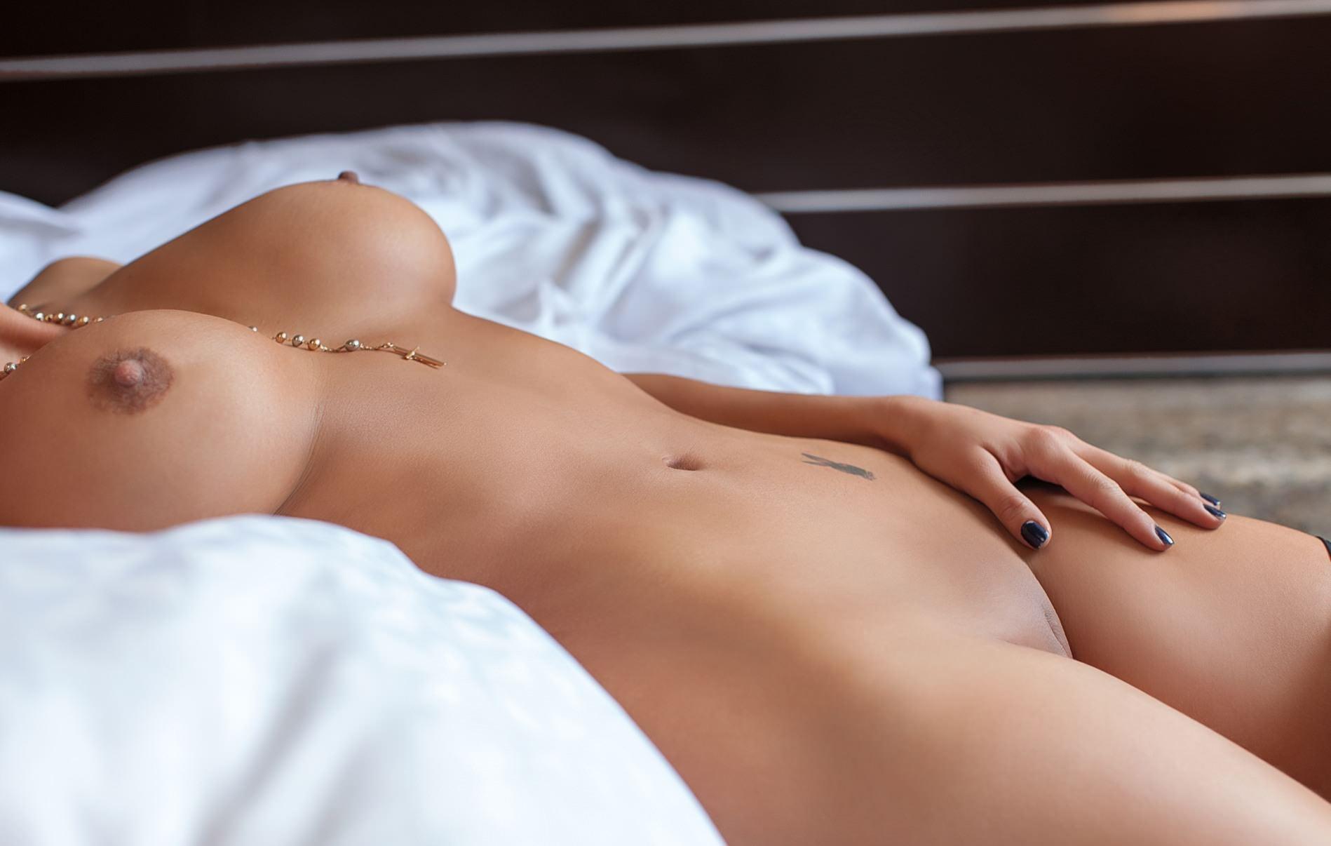 Фото Сексуальное обнаженное женское тело в постели, большие классные сиськи, бритая киска, рука гладит бедро, мелкое тату у пупка, соски, цепочка между сисек, скачать картинку бесплатно