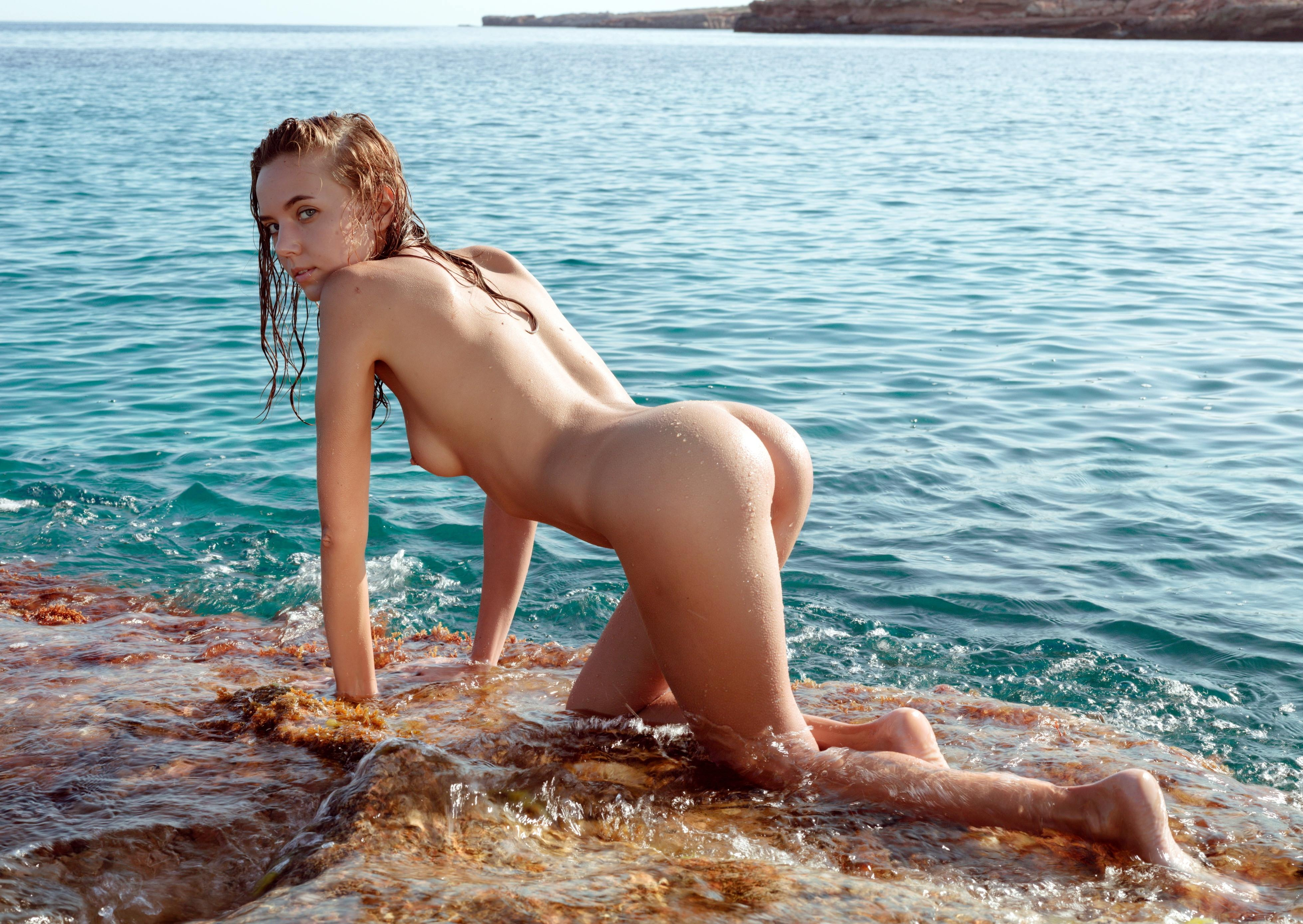 Фото Обнаженная молодая девушка ползет на четвереньках по мокрым камням вдоль берега, мокрая попка, скачать картинку бесплатно
