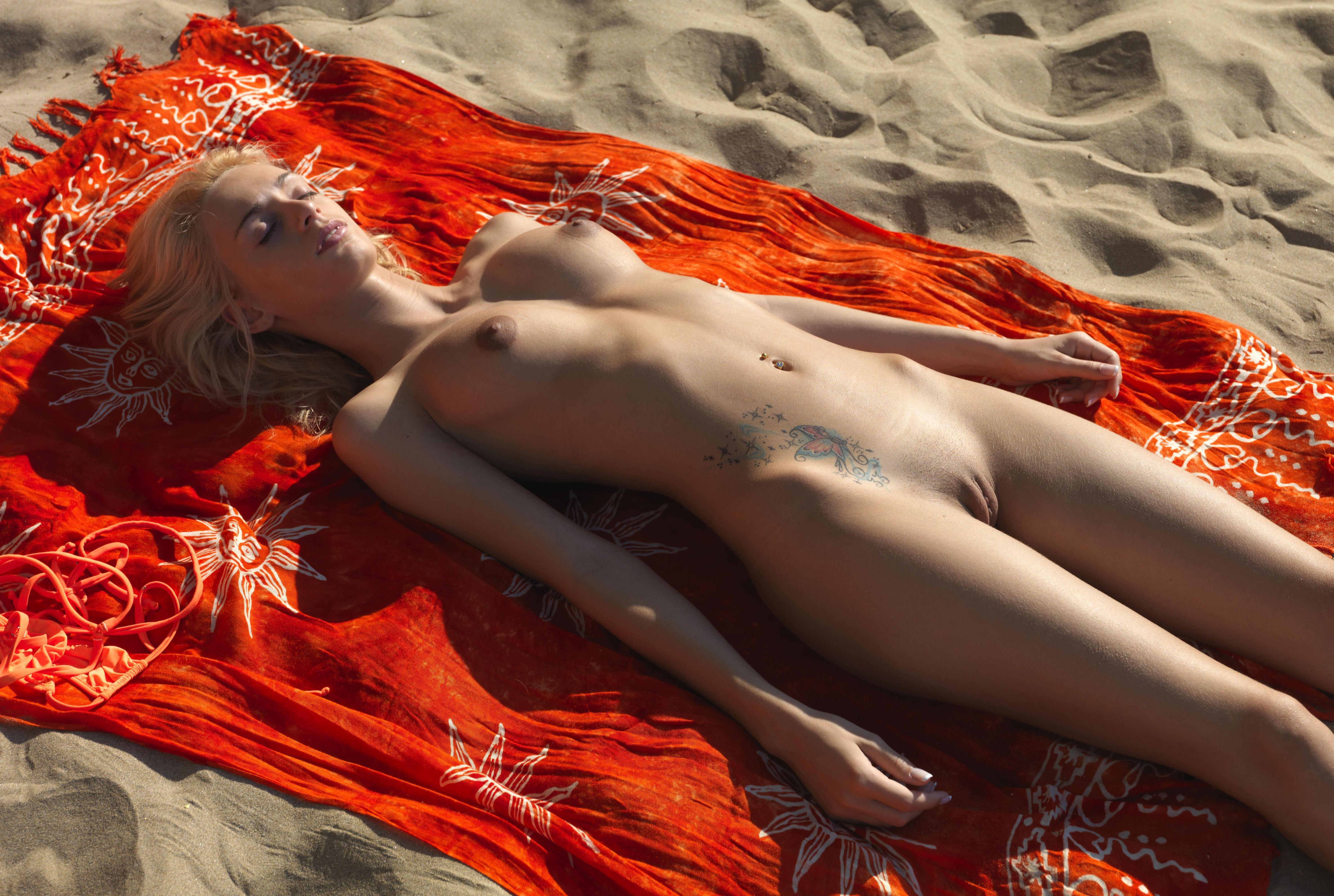 Фото Голая блондинка уснула на пляже, соски набухли,тату на животе, горячий песок, бритая киска, сочная пизда молодой девчонки на пляже, скачать картинку бесплатно