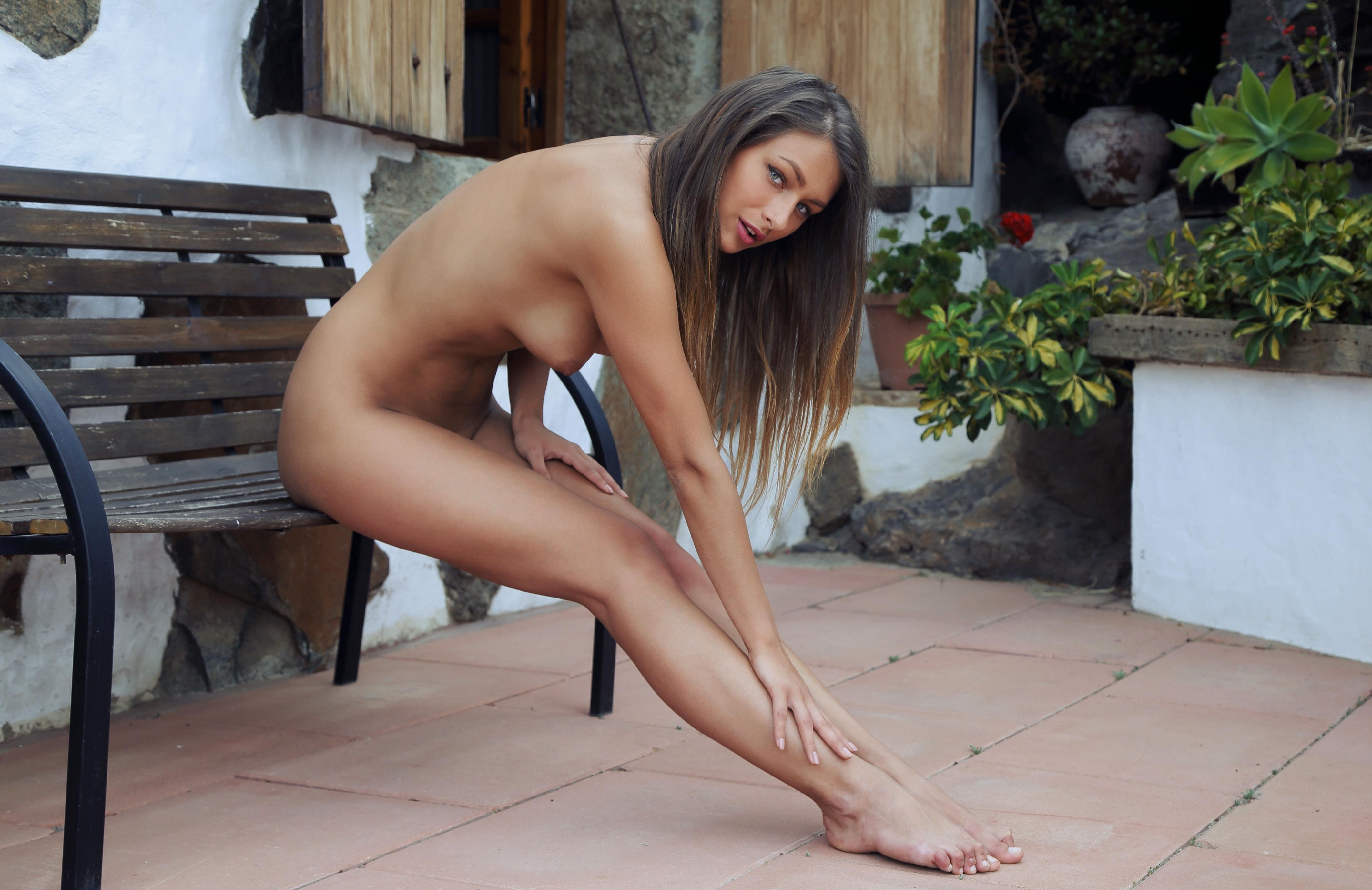 Фото Обаятельная голая девушка гладит ножки, сидя на лавке у дома, красивые нежные ножки обнаженной брюнетки, сидящей на скамье, скачать картинку бесплатно