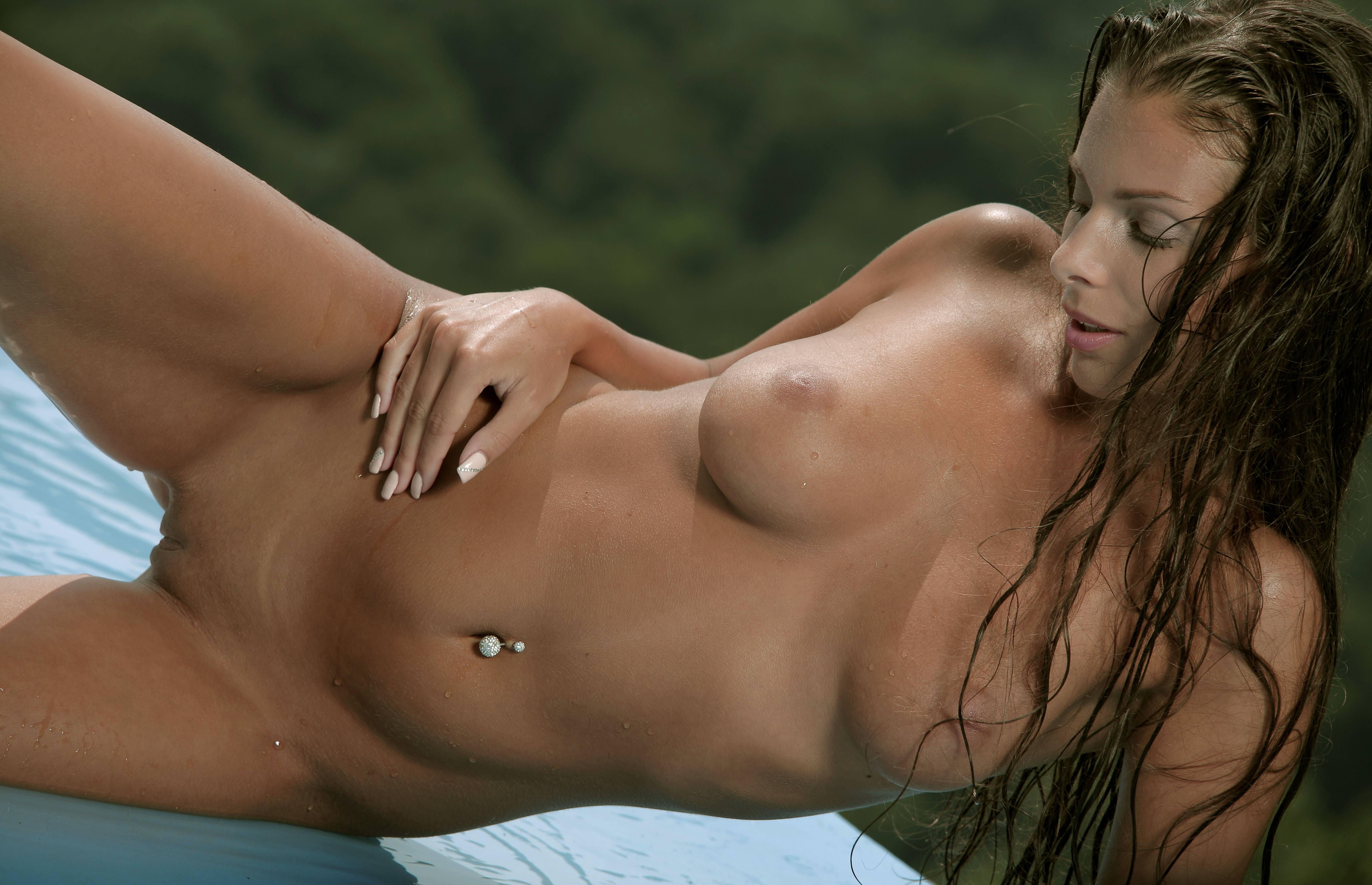 Фото Голая загорелая девушка возбужденно извивается на мокром матрасе, пирсинг в пупке, бритая мокрая киска между ног, скачать картинку бесплатно