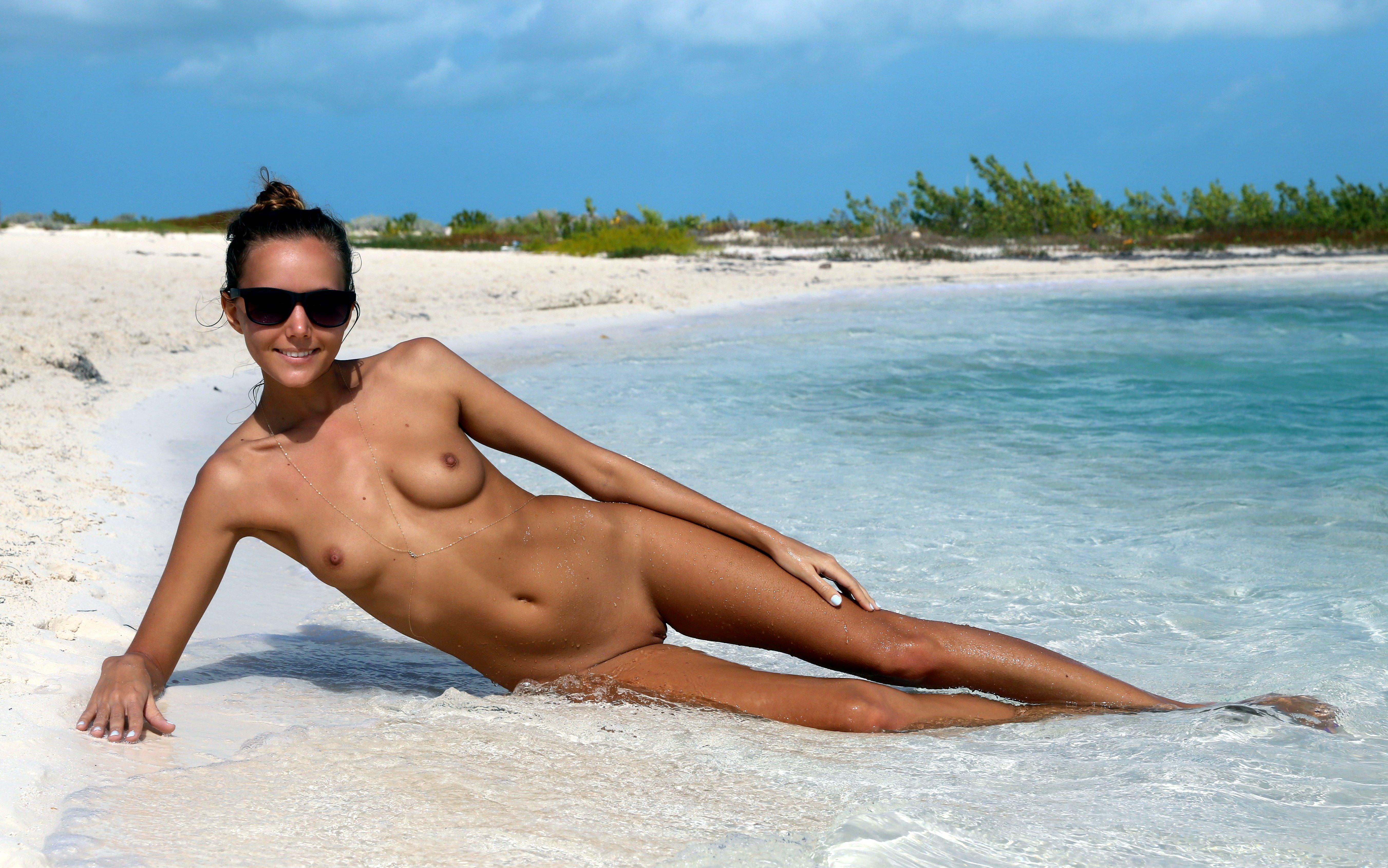 Фото Голая жизнерадостная девушка позирует голая на берегу моря в темных очках, загорелое сексуальное тело, ножки в воде, скачать картинку бесплатно