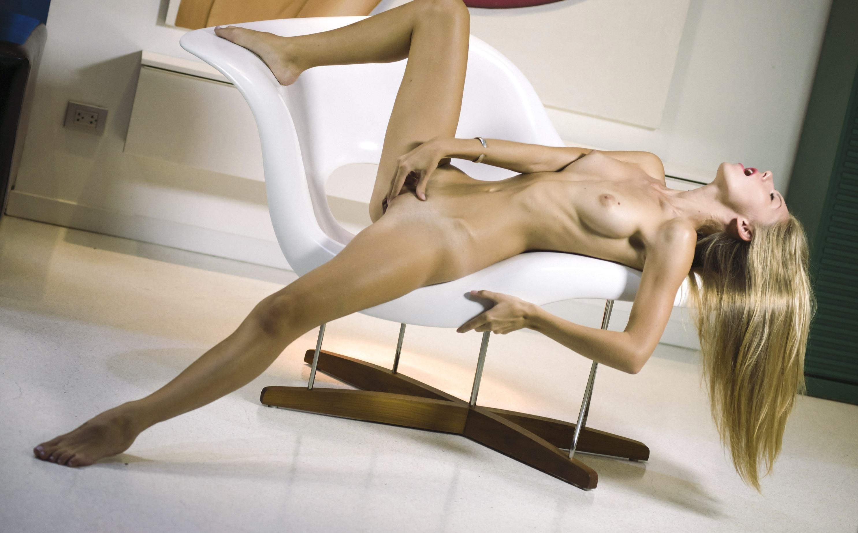 Фото Голая девушка сжимает клитор в кресле, ласкает промежность, скачать картинку бесплатно