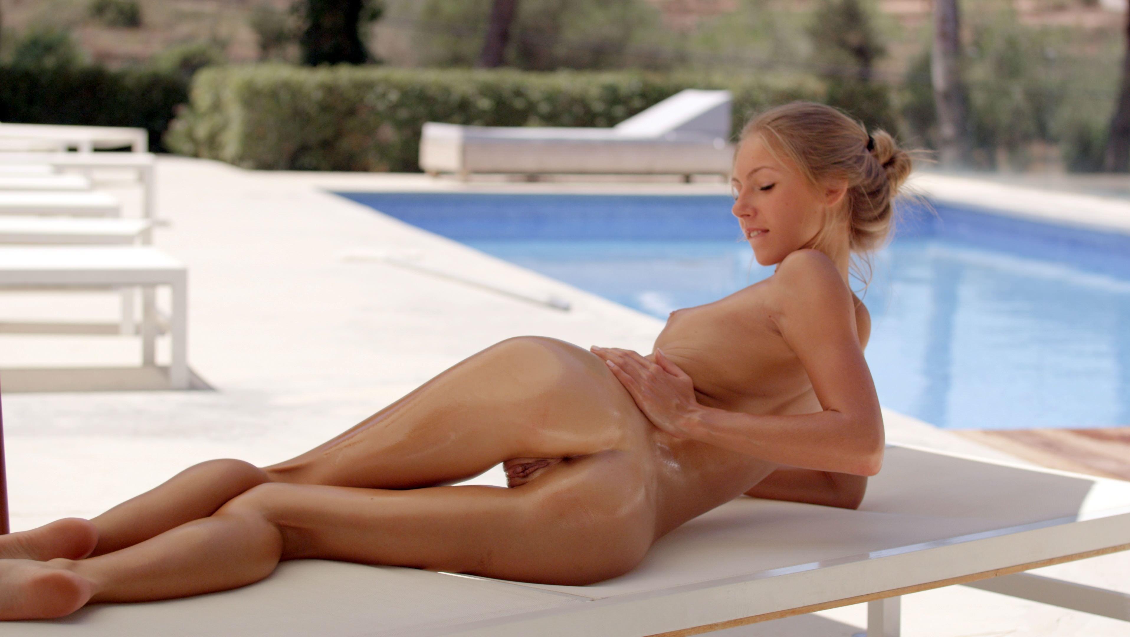 Фото Голая загорелая девушка мажет себя маслом, гладит попу и спинку, блестящие ляжки, бассейн, скачать картинку бесплатно