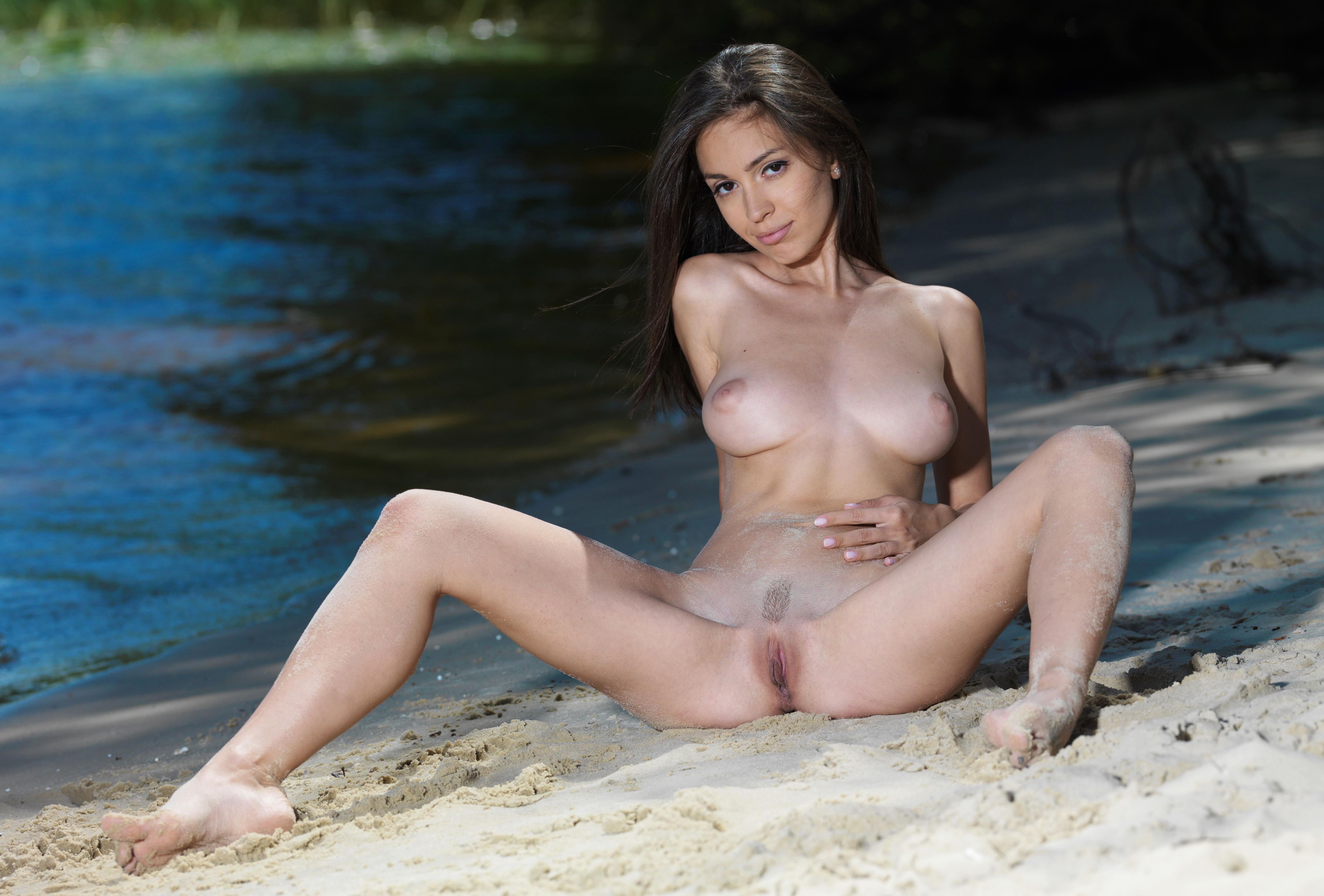 Фото Обнаженная соблазнительная брюнетка ласкает животик на песке, раздвинула ноги у озера, скачать картинку бесплатно