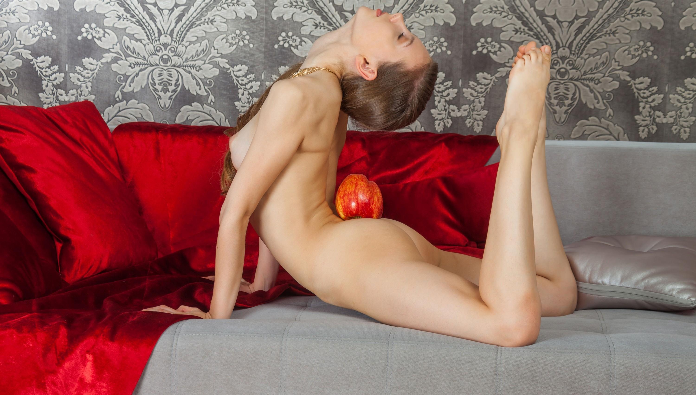 Фото Голая девчонка вытягивается на диване, яблоко на попе, скачать картинку бесплатно
