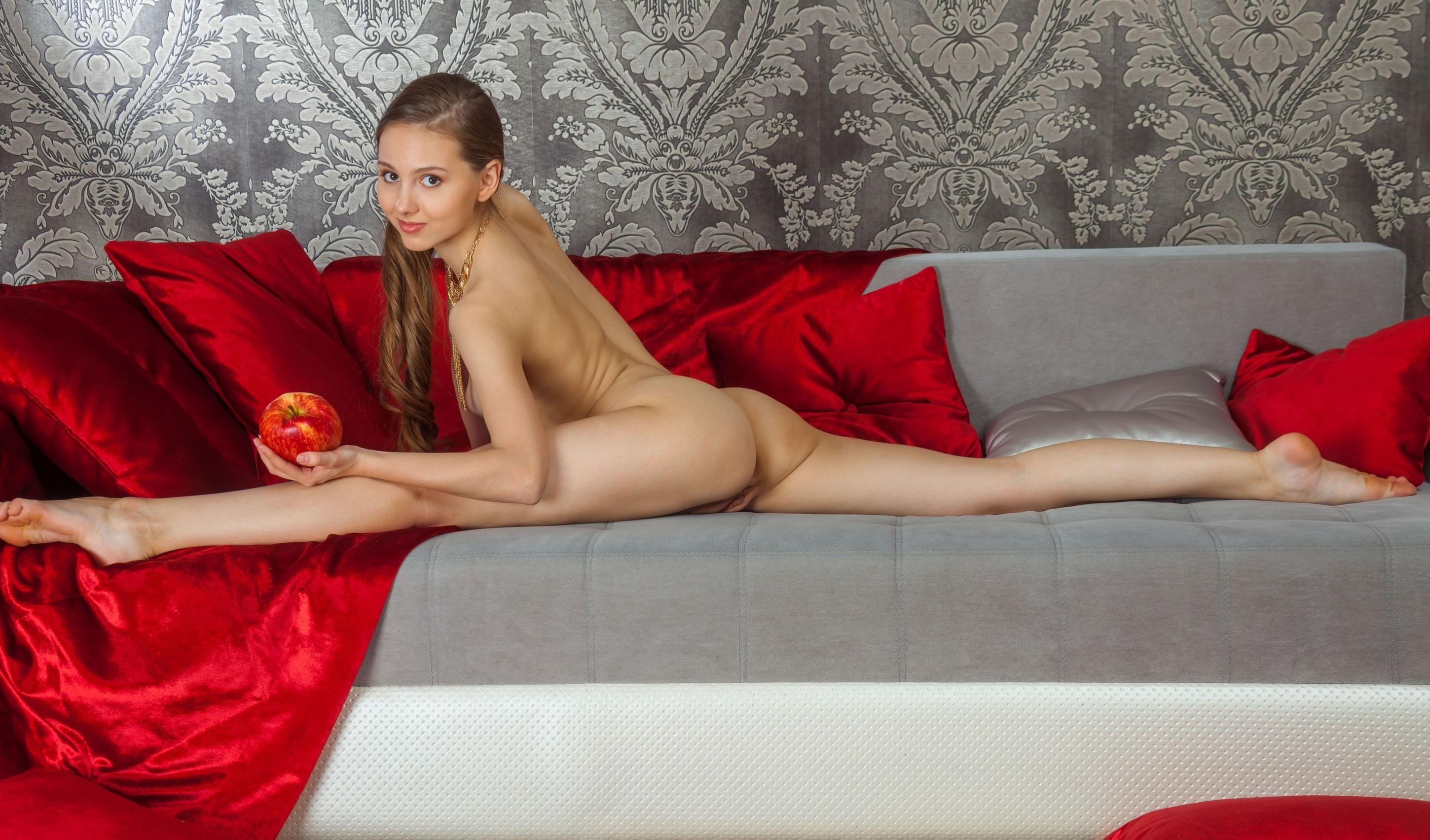 Фото Голая девчонка делает шпагат на диване, яблоко в руке, красные подушки, скачать картинку бесплатно