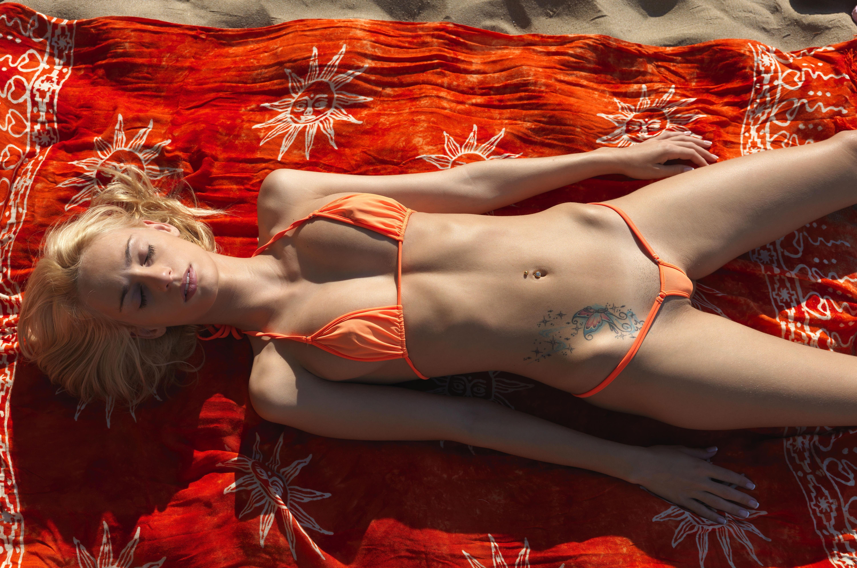Фото Блондинка в оранжевом мини бикини загорает на пляже, тату на животе, закрыла глаза и расслабилась, красное покрывало, пляж, скачать картинку бесплатно