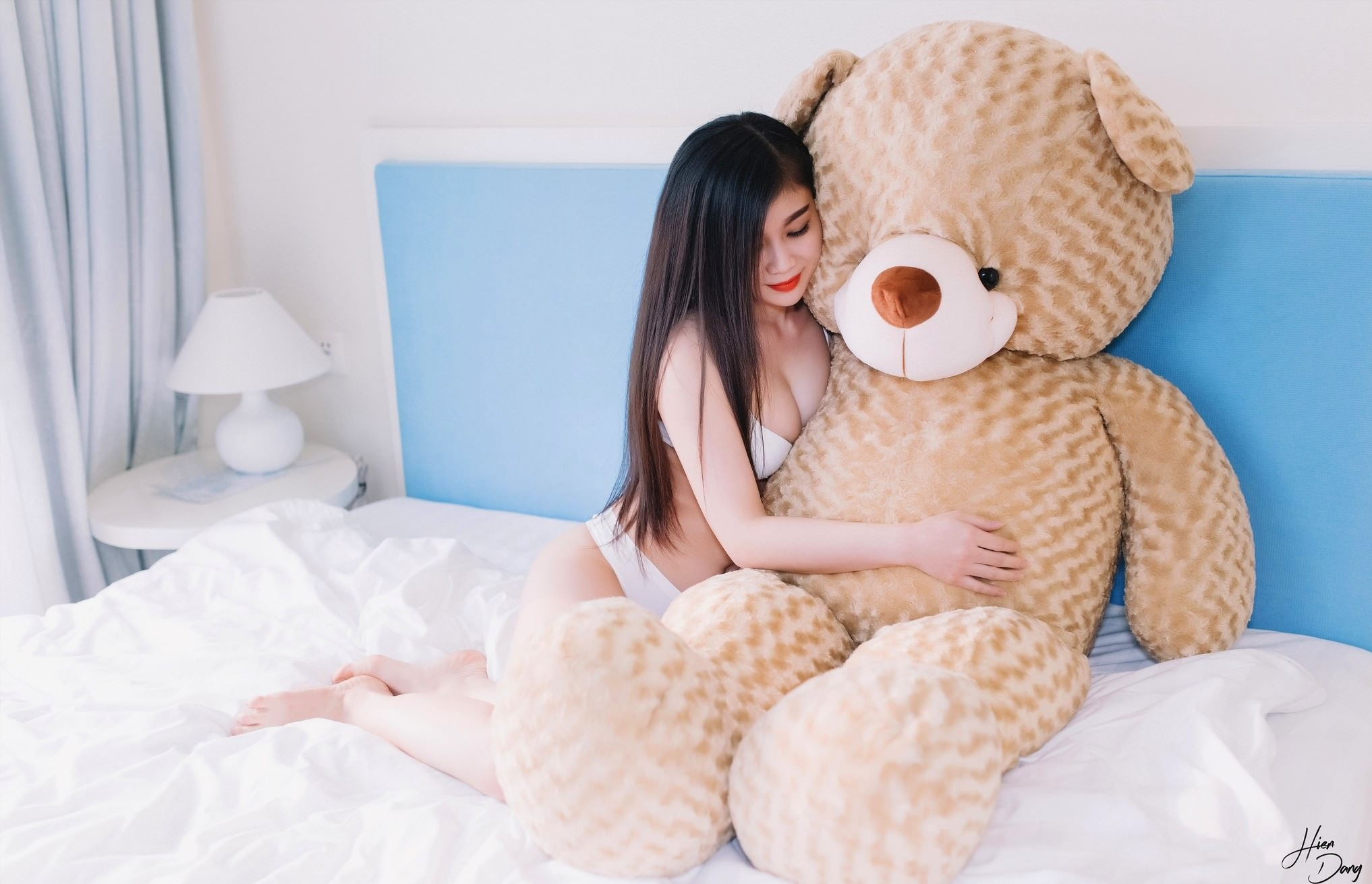 Фото Красивая азиатка обнимает большого плюшевого мишку в постели, японка в белом нижнем белье, красные губки, скачать картинку бесплатно