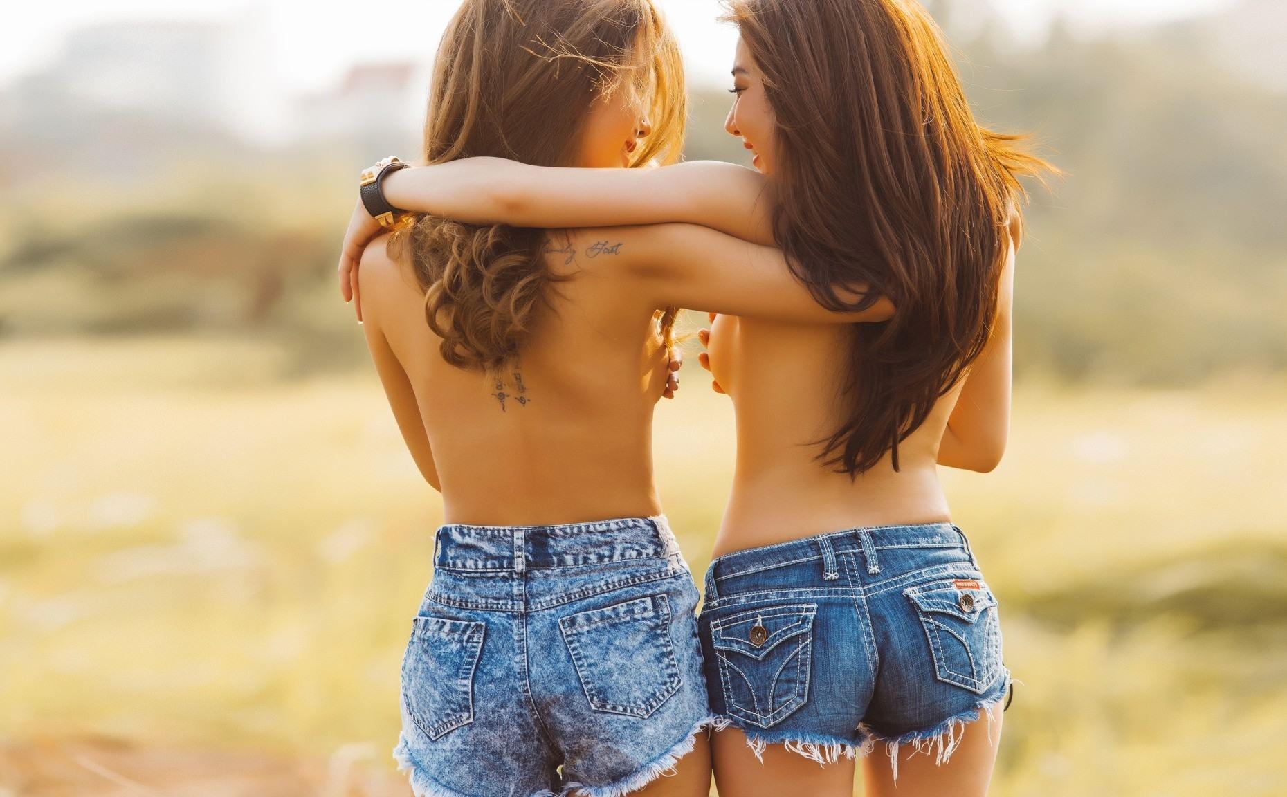 Фото Две веселые подруги в джинсовых шортиках обнимаются и идут по полю без лифчиков, скачать картинку бесплатно