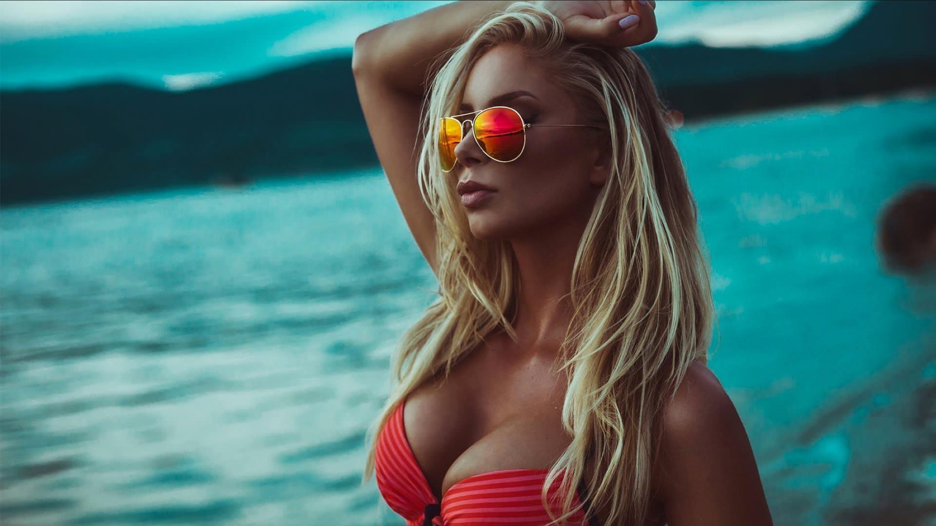 Фото Блондинка в красном бикини, упругая грудь, море, пляж, сумерки, очки, скачать картинку бесплатно