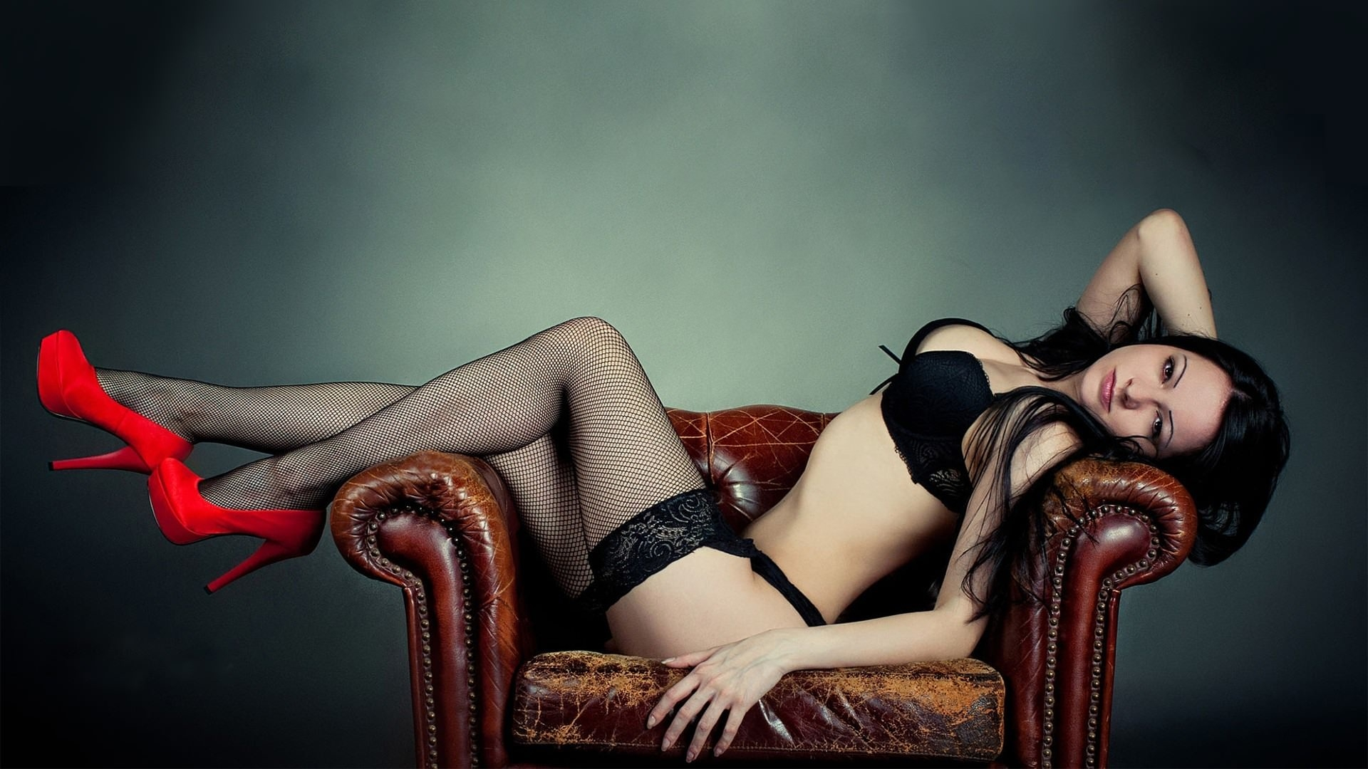 Фото Сексуальная брюнетка в красных туфлях, сексуальные ножки в чулочках, эротично развалилась в кресле, скачать картинку бесплатно
