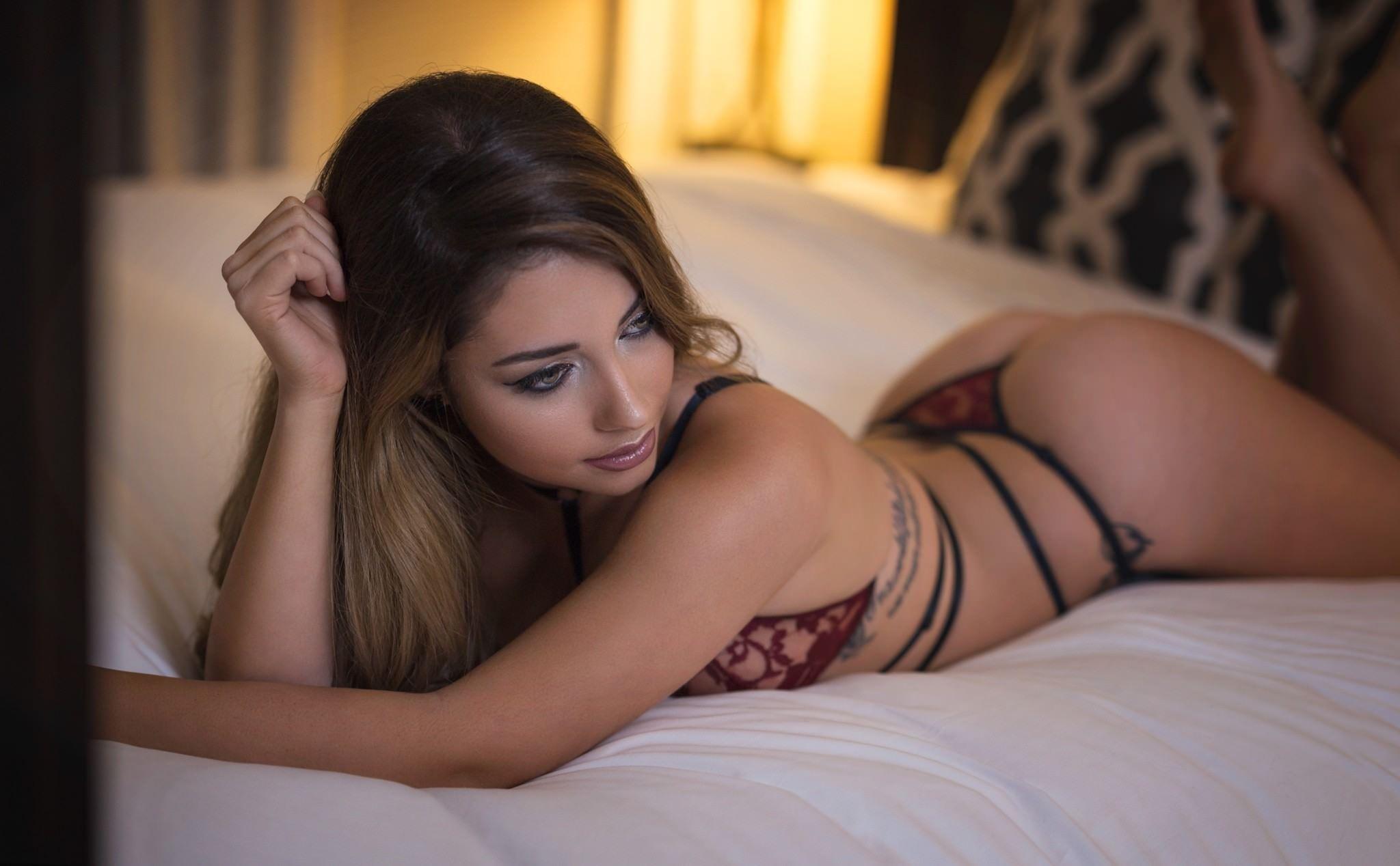 Фото Бордовые стринги на попе, красивая девушка в нижнем белье задумчиво лежит на кровати, скачать картинку бесплатно