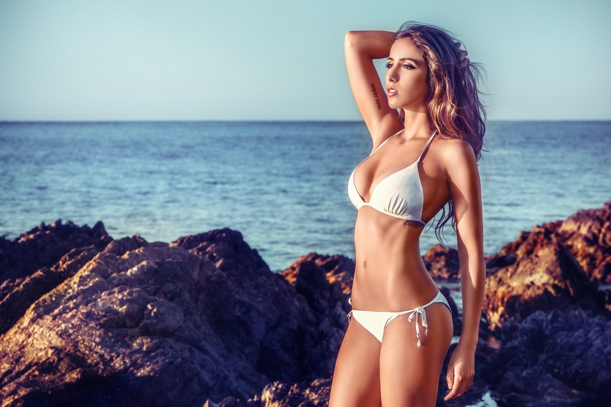 Фото Девушка в белом бикини, море, камни, горизонт, закат, скачать картинку бесплатно