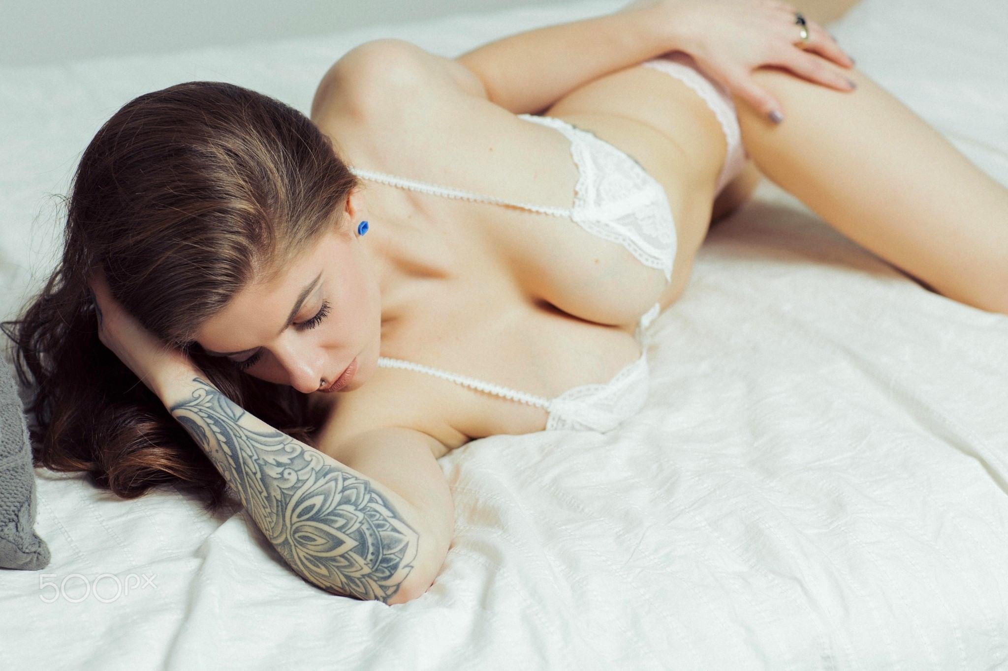 Фото Брюнетка в белом нижнем белье, тату на руке, большая грудь, постель, скачать картинку бесплатно