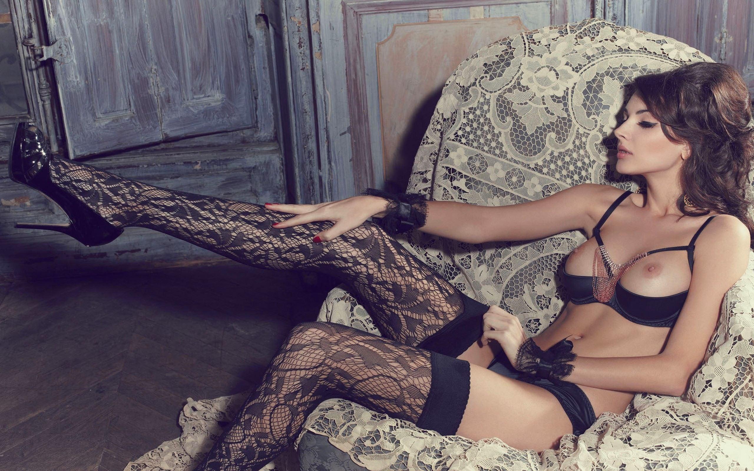 Фото Сексапильная девушка в черных узорчатых чулках, вытянула сексуально ножку, сидя в кресле, лифчик, не скрывающий сиськи, гладит колено, брюнетка в эротическом белье, скачать картинку бесплатно