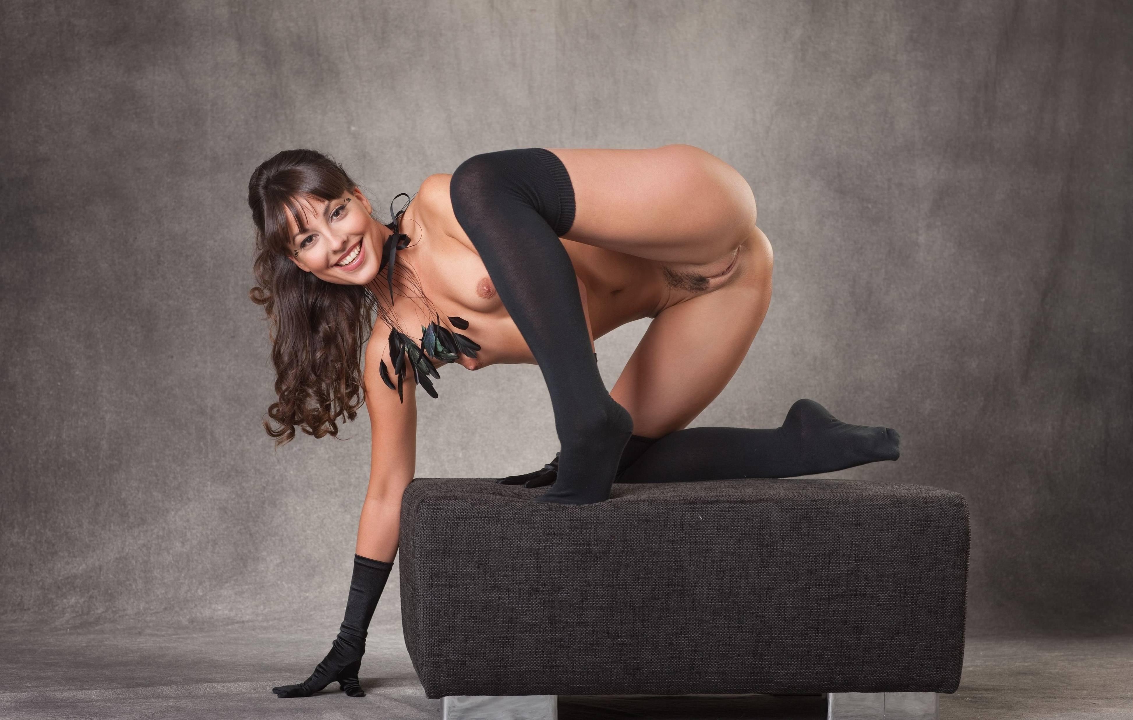 Фото Улыбающаяся девушка в черных гольфах, без нижнего белья на пуфике, скачать картинку бесплатно