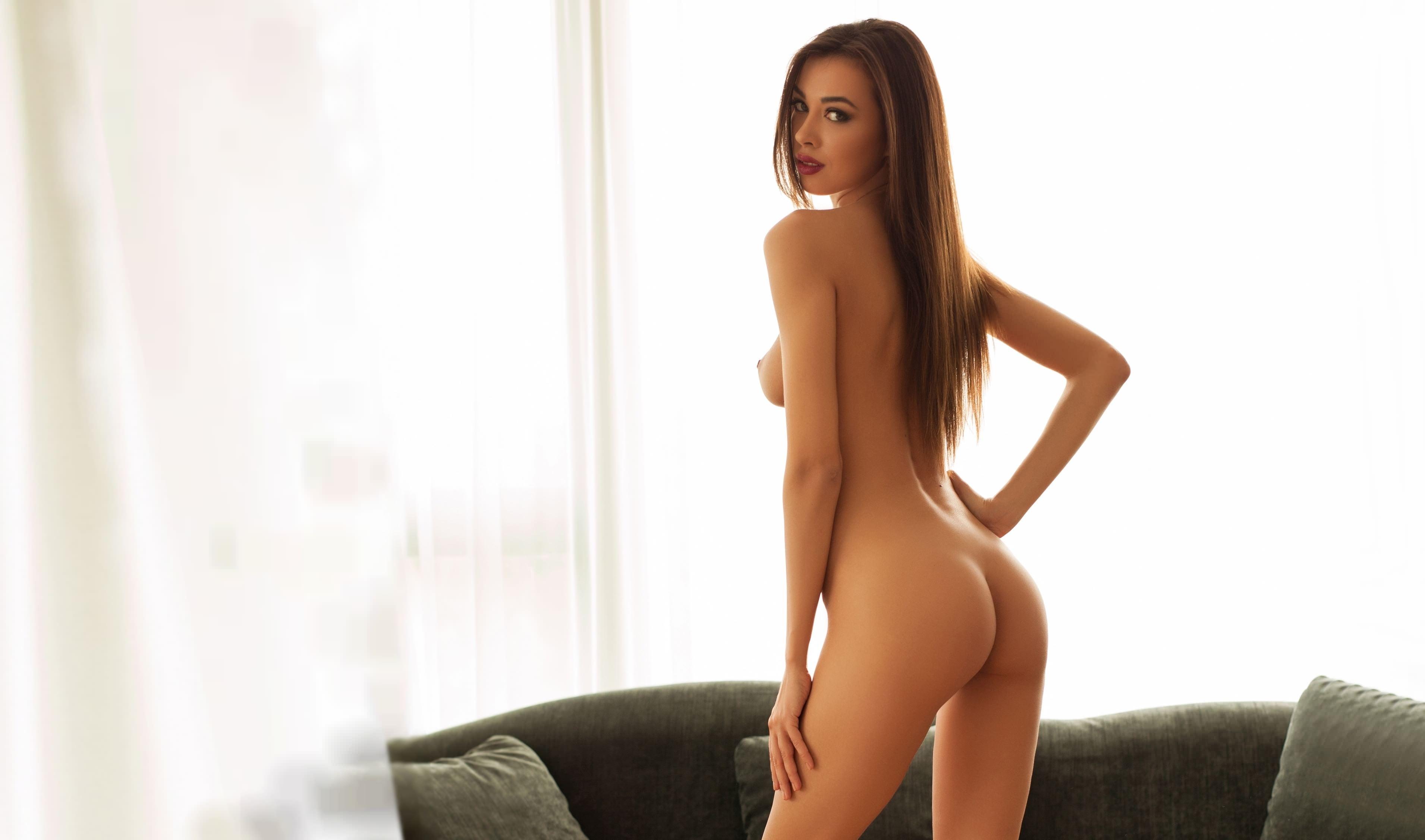 Фото Голая девушка грациозно стоит у дивана, скачать картинку бесплатно