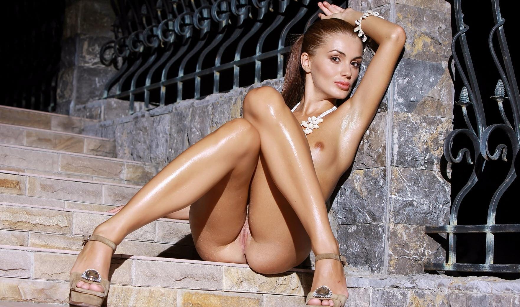 Фото Голая девушка намазала свое сексуальное тело маслом, позирует на лестнице, сексуальные блестящие ножки, попка прижалась к лестнице, скачать картинку бесплатно