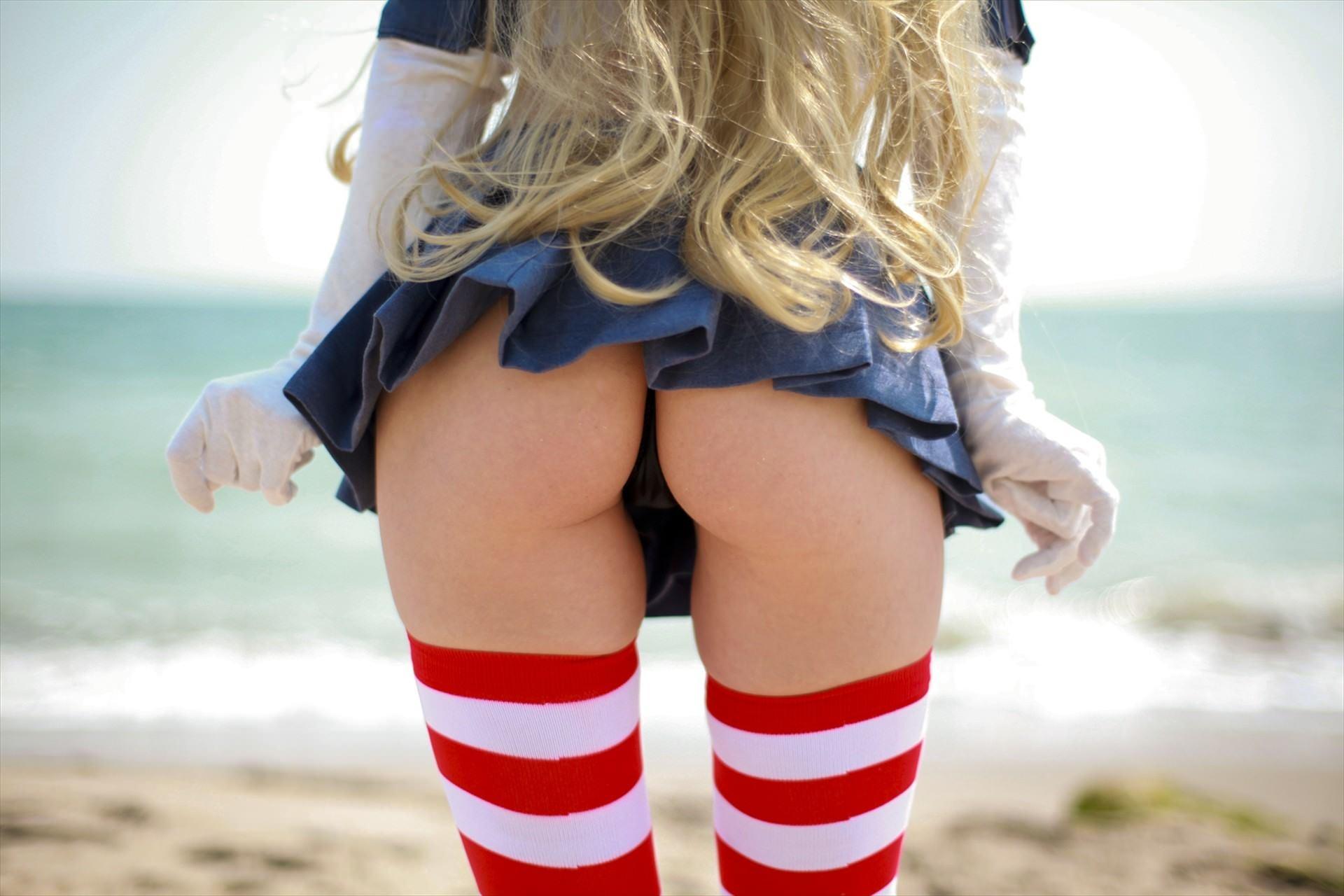 Фото Блондинка в синей мини юбке, стринги на упругой попке, красно-белые полосатые гольфы, пляж, скачать картинку бесплатно