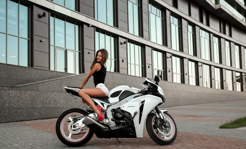 Фото Красивая сексуальная брюнетка позирует на сиденье спортивного мотоцикла, секси девушка в черной майке и белых шортиках на Хонде, скачать картинку бесплатно
