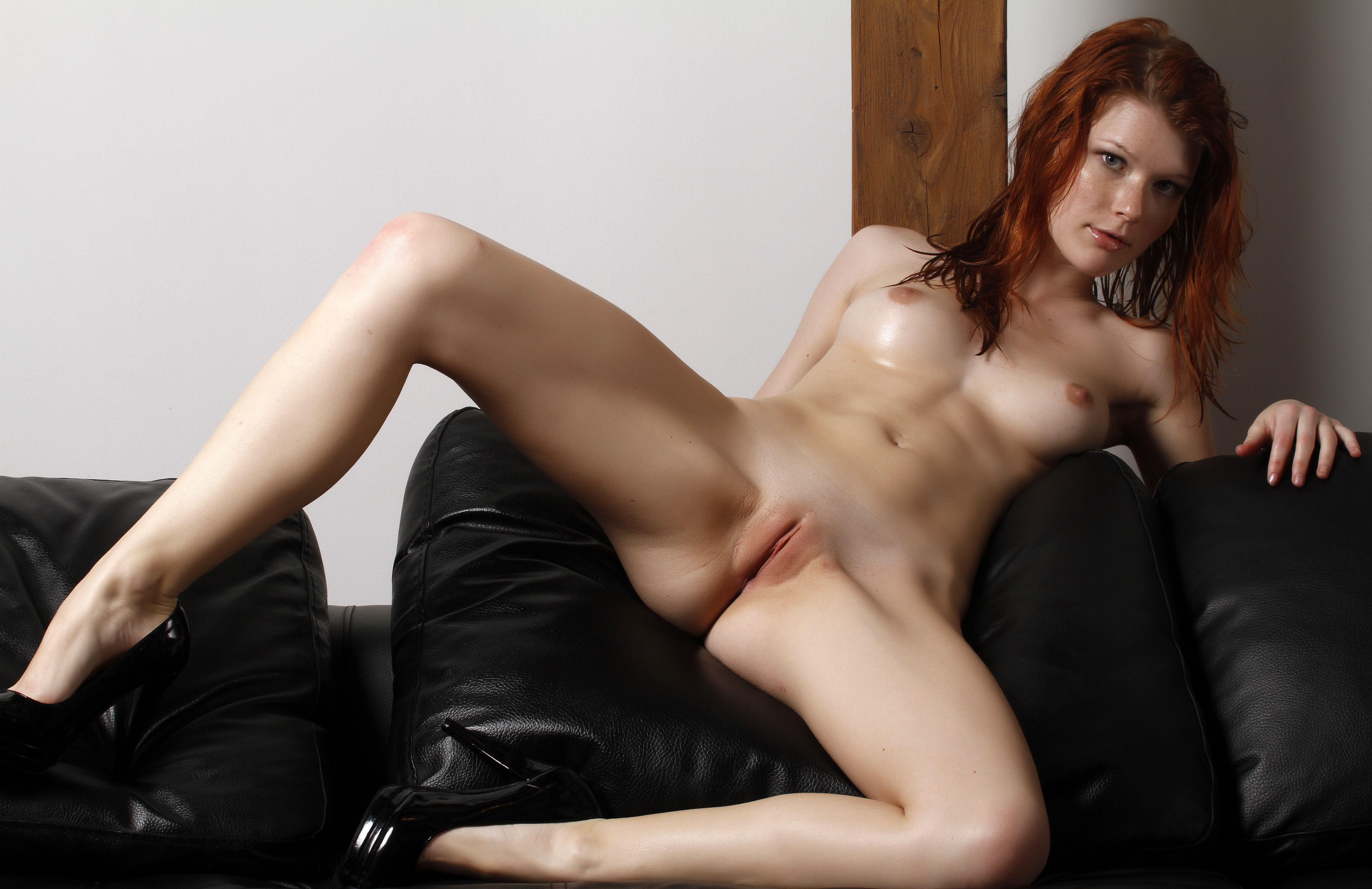 Фото Голая рыжеволосая девушка раздвигает ноги на черном кожаном диване, бритая пися, сексуальное тело, сочные ляжки, сексуальные ножки, скачать картинку бесплатно