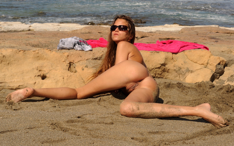 Фото Обнаженная девушка в темных очках извивается на песке, сексуальная попа, море, ножки в песке, скачать картинку бесплатно