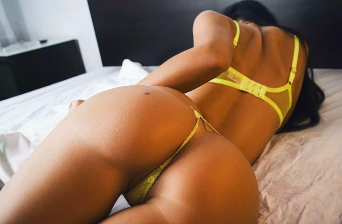 Фото Сексуальное и желанное тело горячей брюнетки в постели, желтые стринги, желтый лифчик, упругая попка с родинкой. Sexy girl on a bed, yellow lingerie, erotic underwear, yellow thongs, bra, brunette, hot, bum birthmark, скачать картинку бесплатно