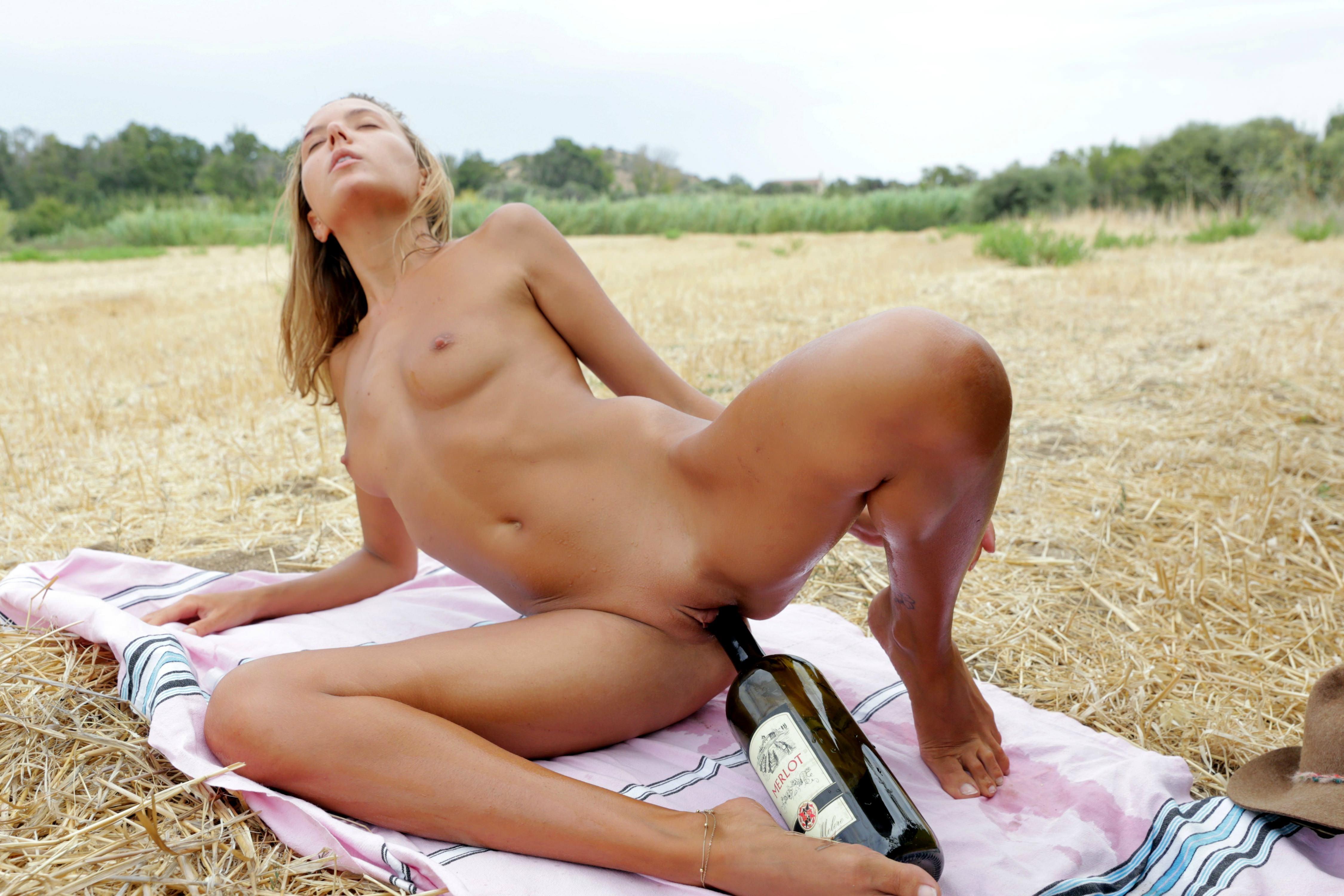 Фото Бутылка вина в пизде, голая загорелая девушка на желтой траве, скачать картинку бесплатно