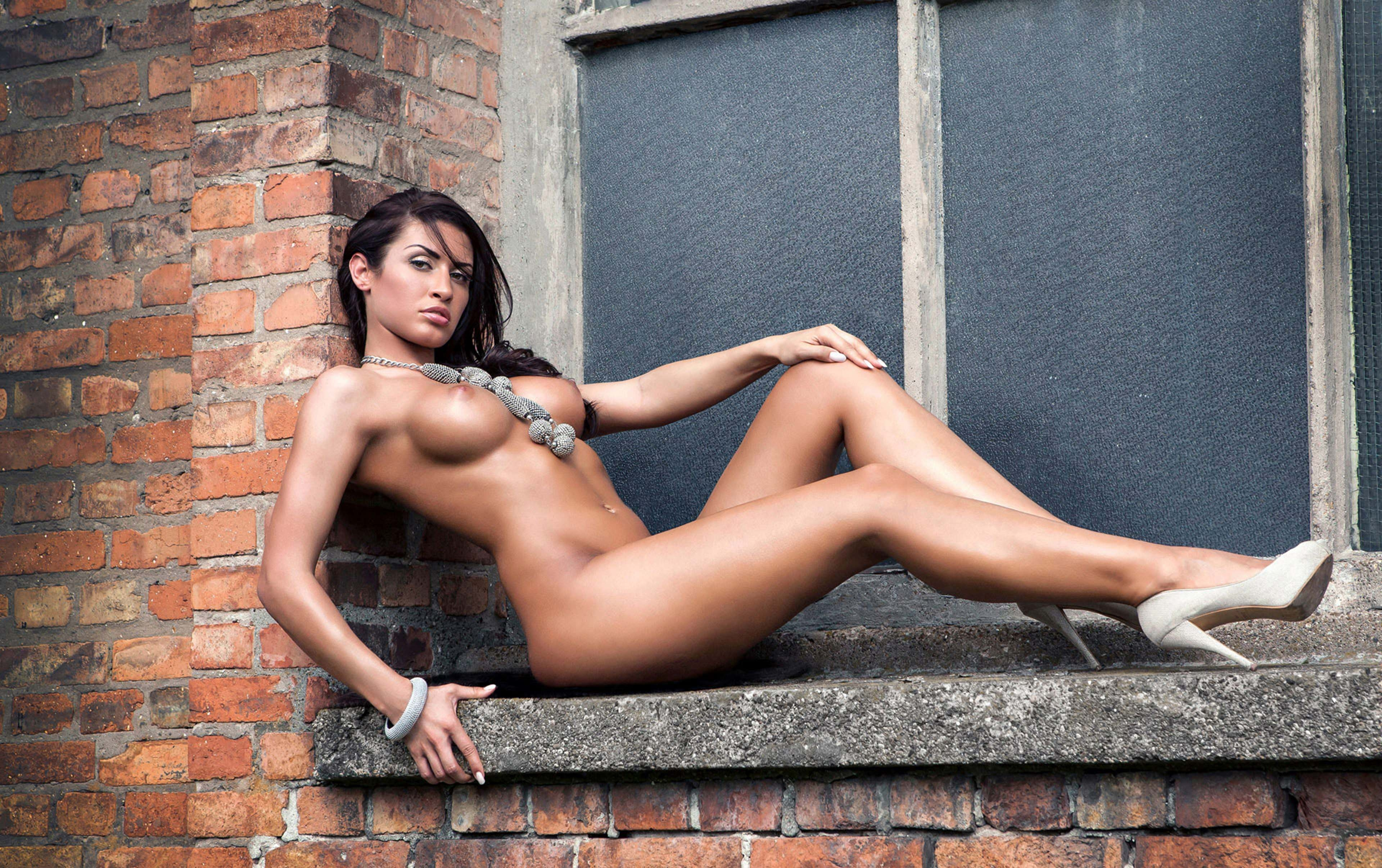 Фото Загорелая голая девушка на подоконнике кирпичного доме снаружи, знойная брюнетка, круглые упругие сиськи, блестящие длинные ножки, скачать картинку бесплатно