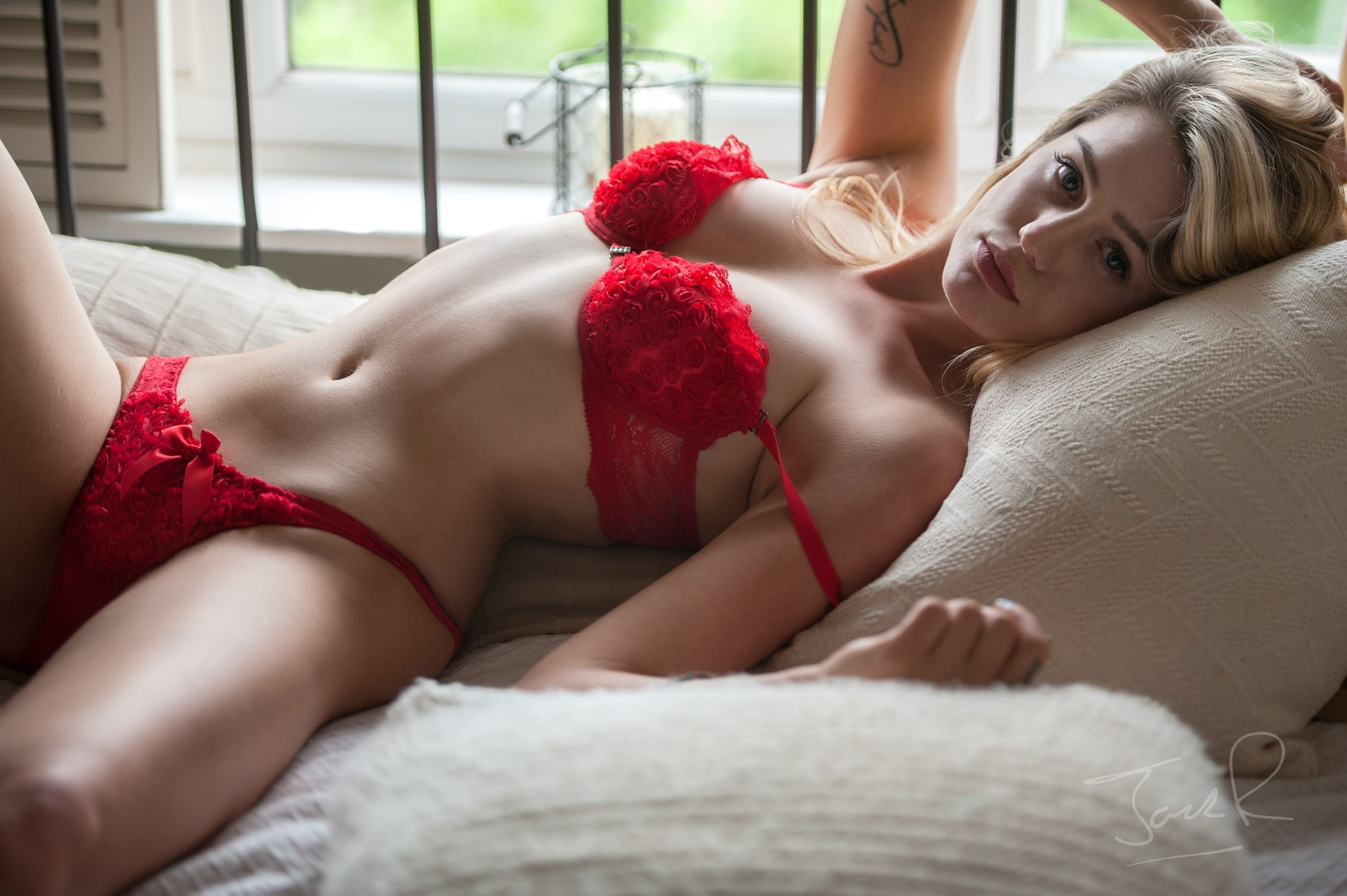 Фото Соблазнительная девушка в красном эротическом нижнем белье, подушки, красные трусики, скачать картинку бесплатно