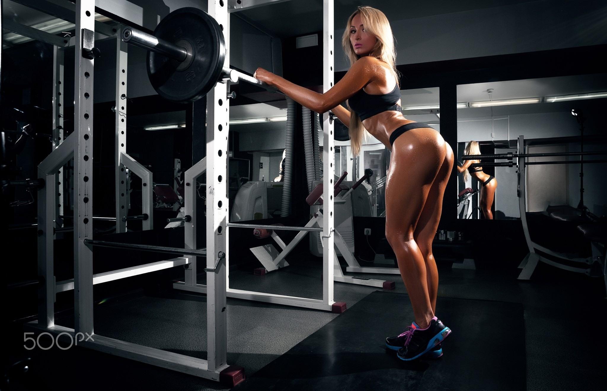Фото Спортивная девушка с шикарной фигурой в тренажерном зале, штанга, блестящие ножки, упругая попка, скачать картинку бесплатно