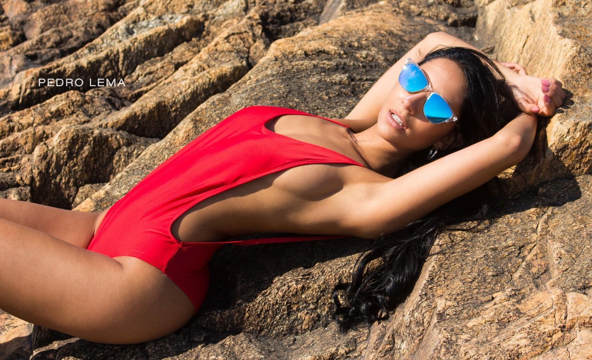 Фото Горячая брюнетка в красном купальнике, шикарная фигура, очки, камни, Pedro Lema, скачать картинку бесплатно