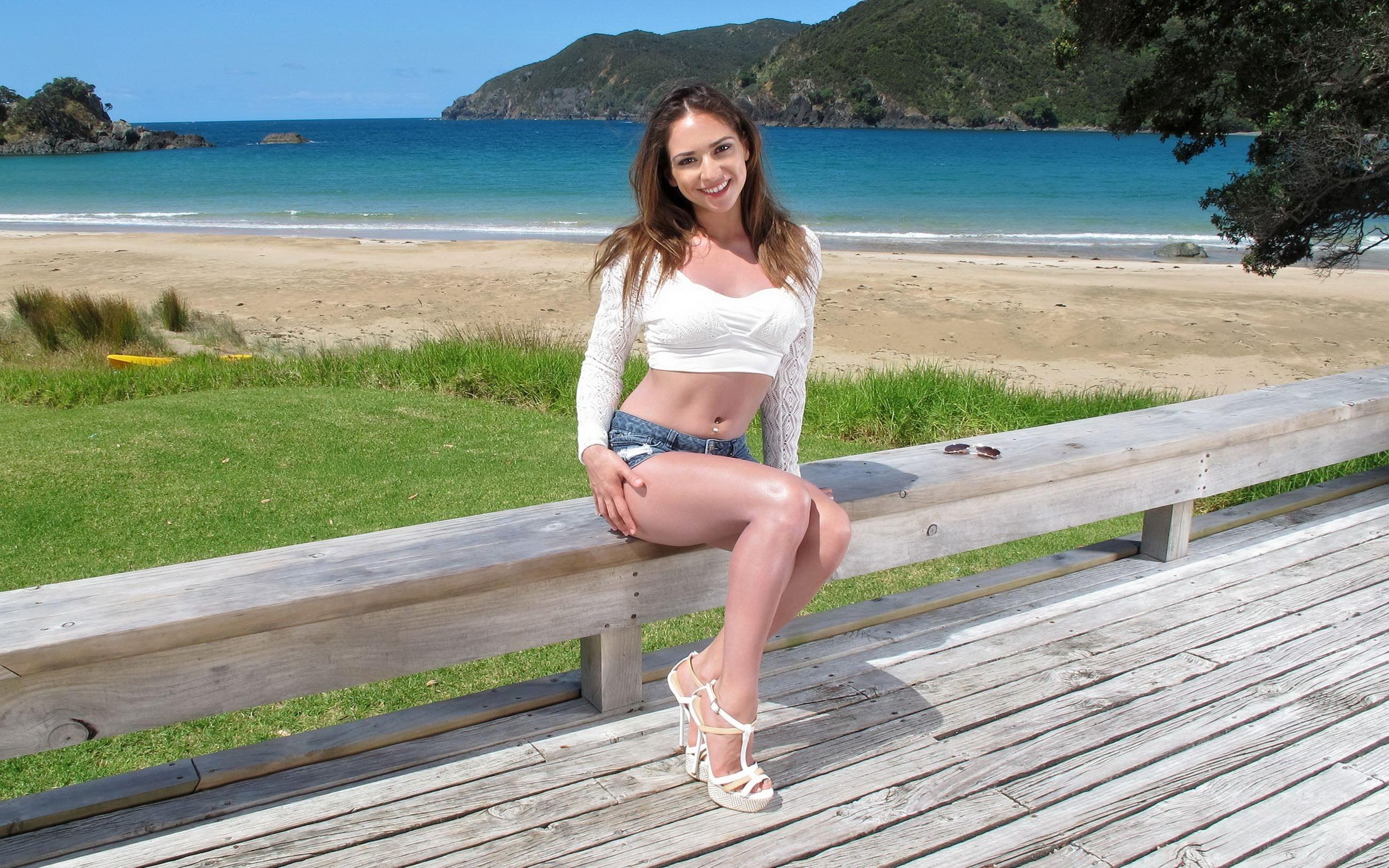 Фото Обаятельная девушка в коротких шортиках и белом топике, блестящие ножки, деревянный пирс, скамья, трава, песок, море, пляж, скачать картинку бесплатно