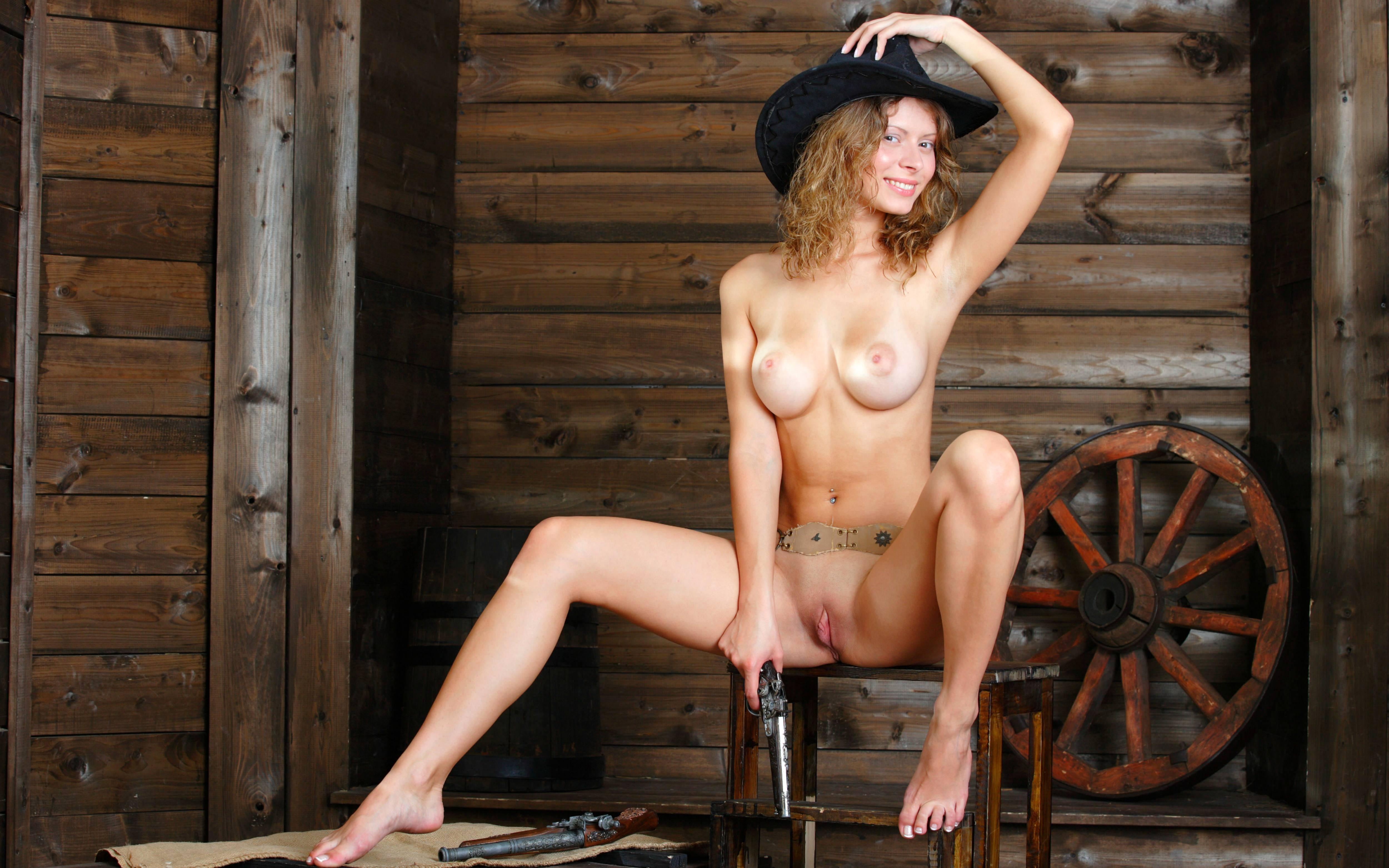 Фото Голая девушка в черной ковбойской шляпе, револьвер в руке, скачать картинку бесплатно
