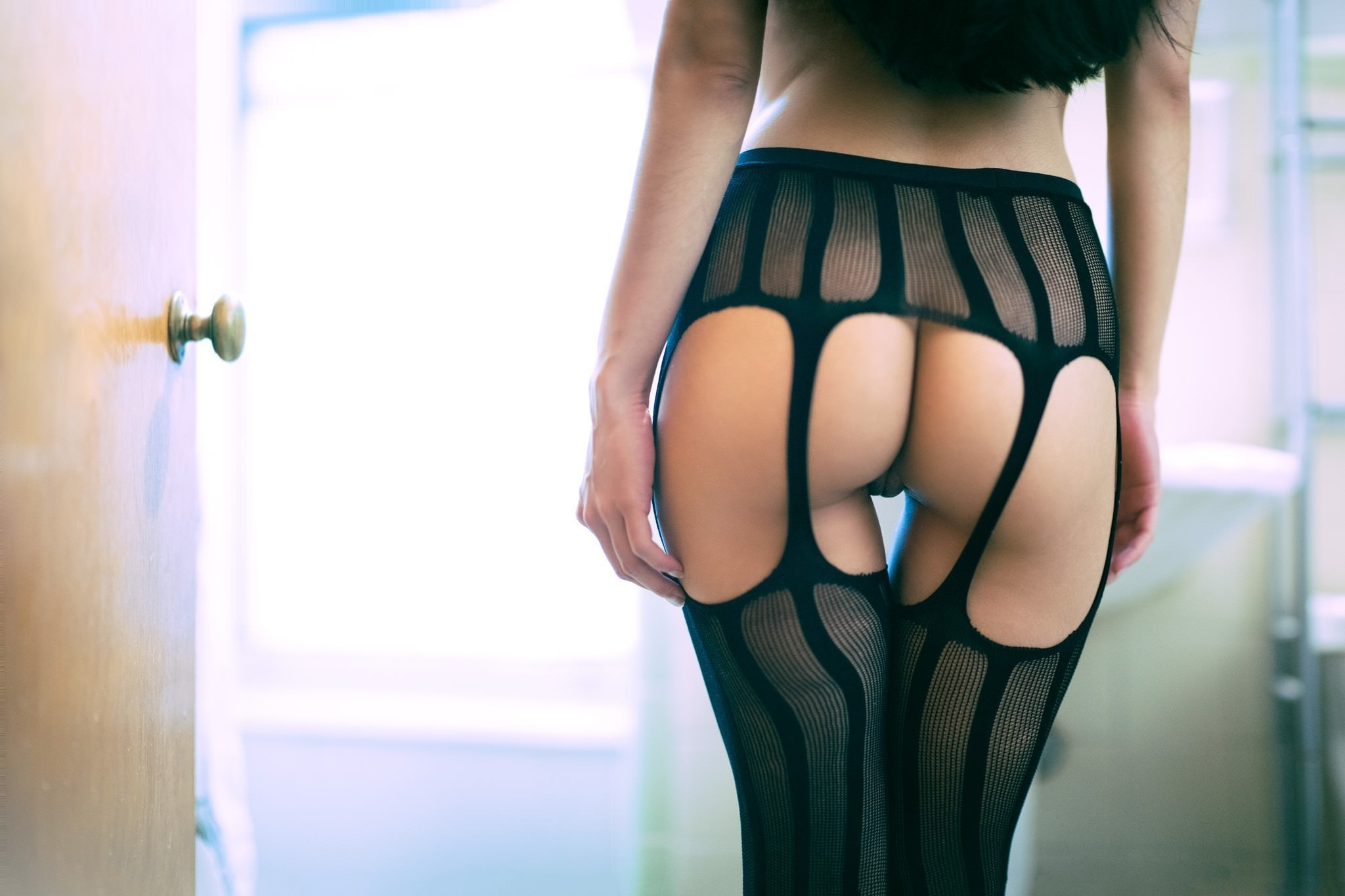 Фото Полосатые черные чулки на подвязках, голая попа, девушка в эротическом белье стоит в комнате, скачать картинку бесплатно