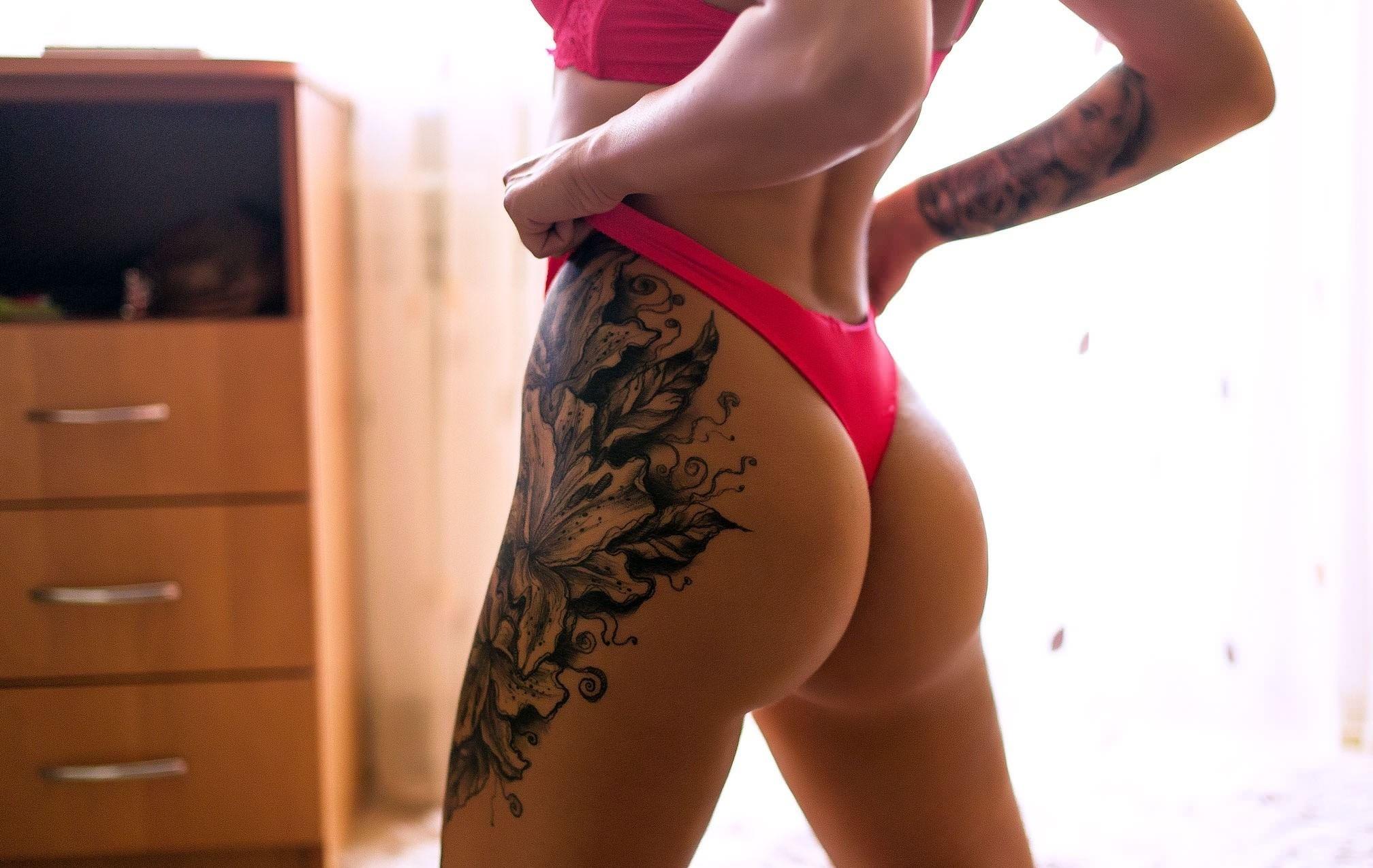 Фото Татуированная спортивная девушка в розовых стрингах, натянула трусики на себе, тату на бедре, скачать картинку бесплатно